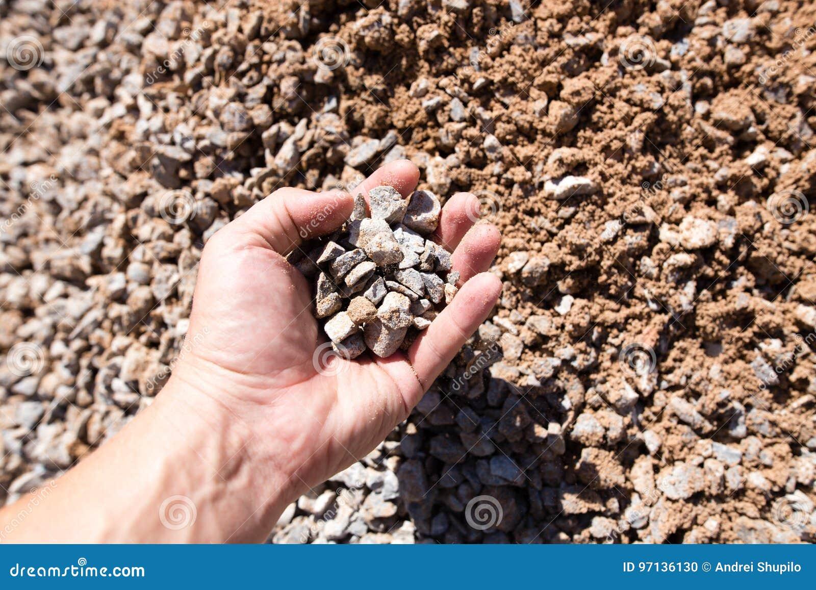 Byggande Krossad Sten Med Sand I Hand Arkivfoto - Bild: 97136130