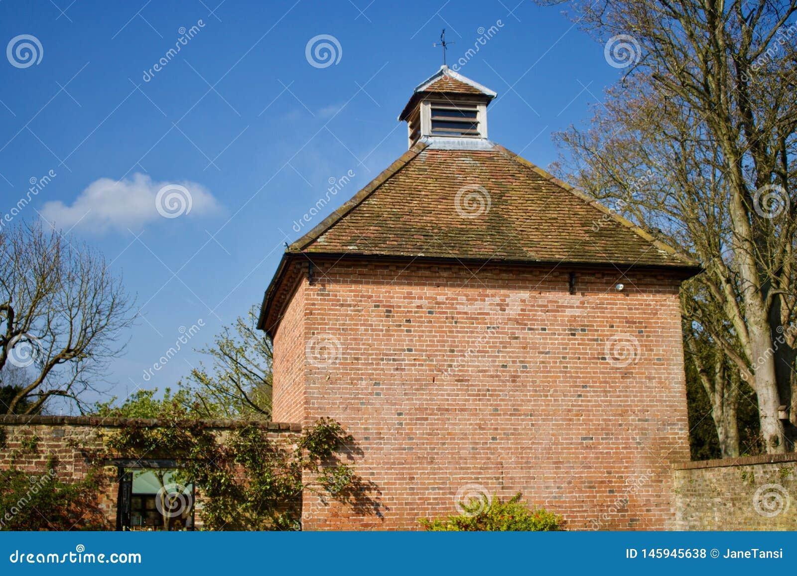 Byggd gammal tegelsten dök skjulet med det belade med tegel taket för terrakottan mot blå himmel - bild