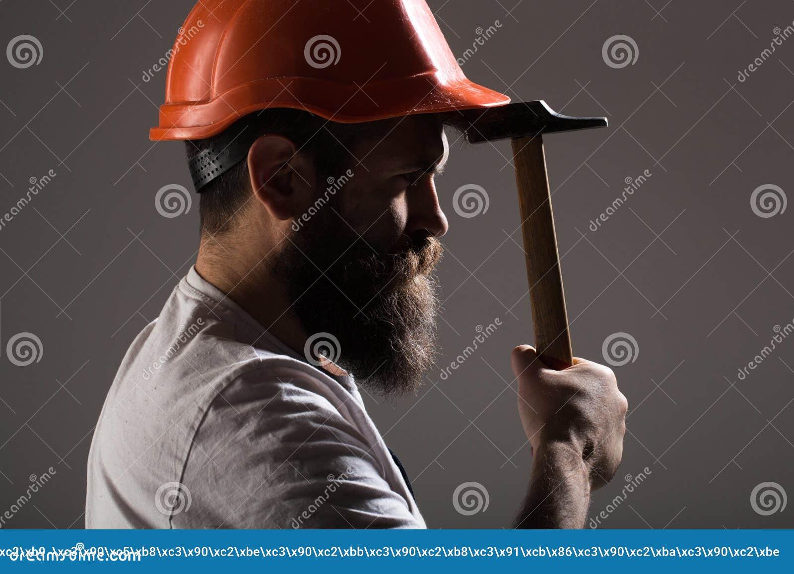 Byggmästare i hjälmen, hammare, faktotum, byggmästare i hardhat Skäggig manarbetare med skägget, byggnadshjälm, hård hatt