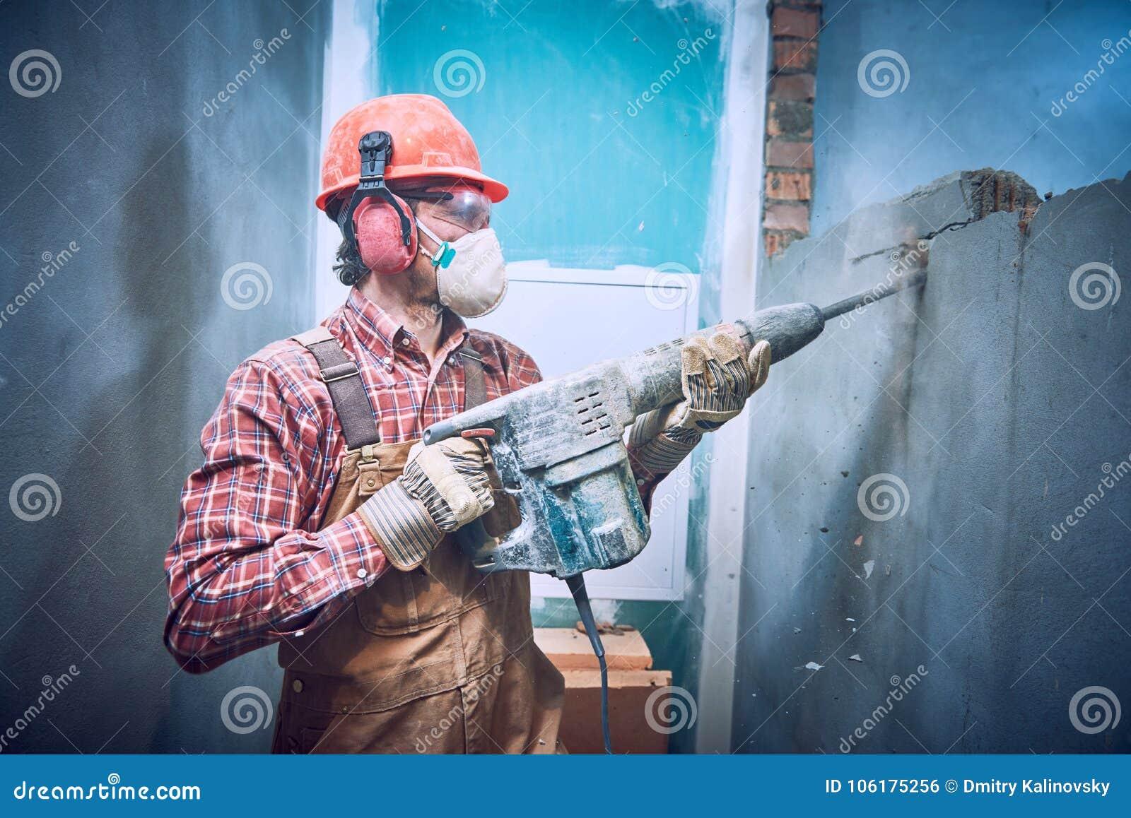 Byggmästare med hammaren som inomhus bryter väggen