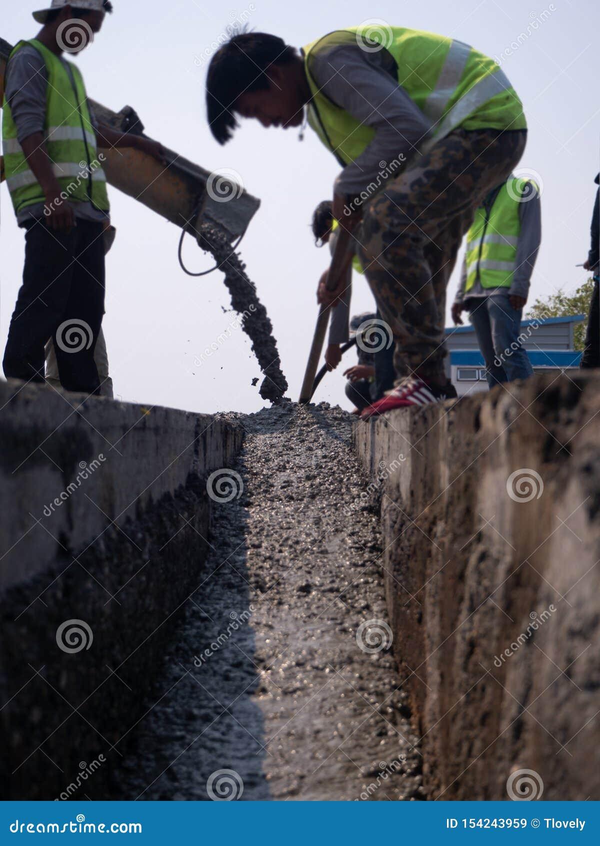 Byggmästare som häller cement under förbättring till den bostads- gatan