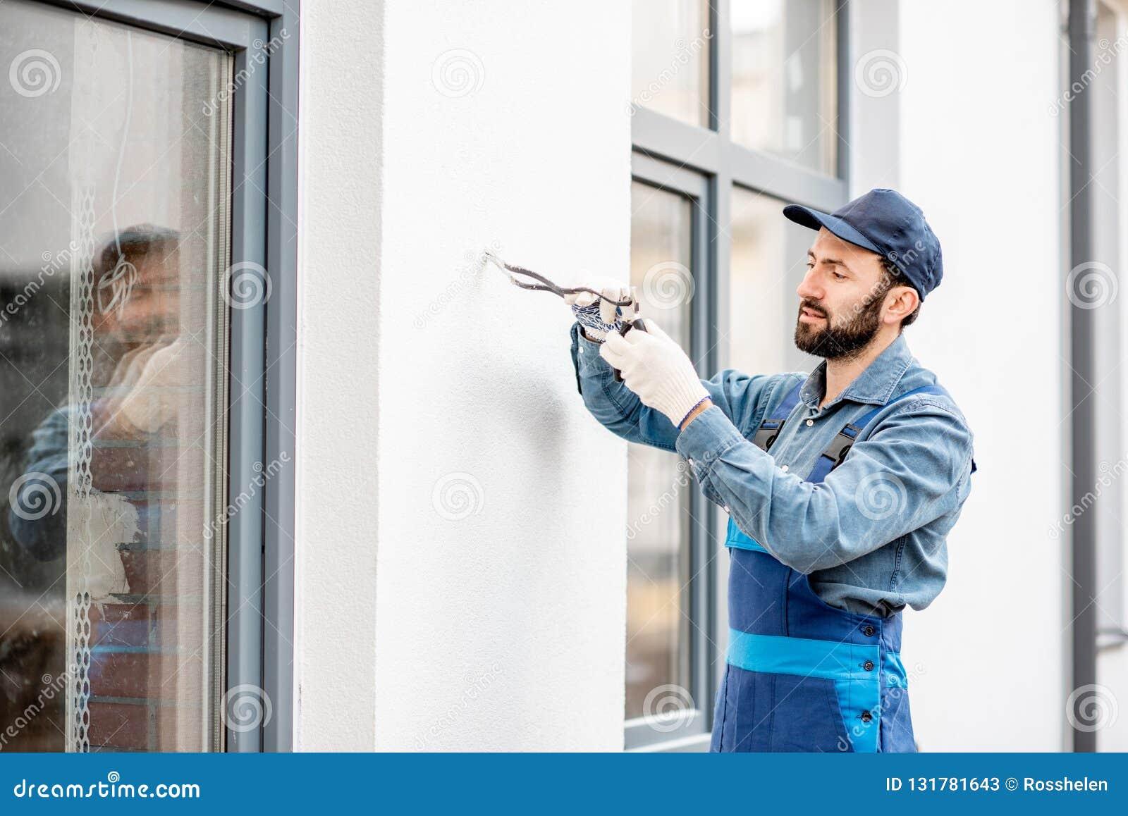 Byggmästare som monterar ledningsnät för utomhus- belysning