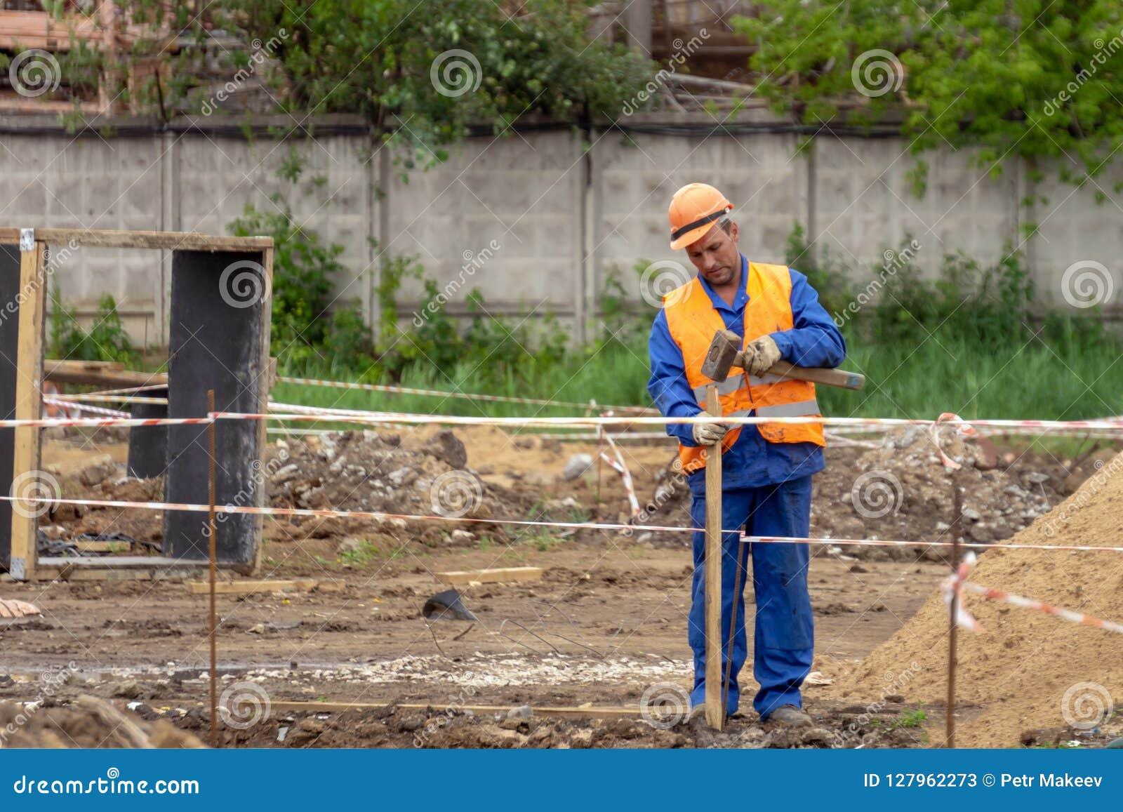 Byggmästaren gör ett staket på konstruktionsplatsen