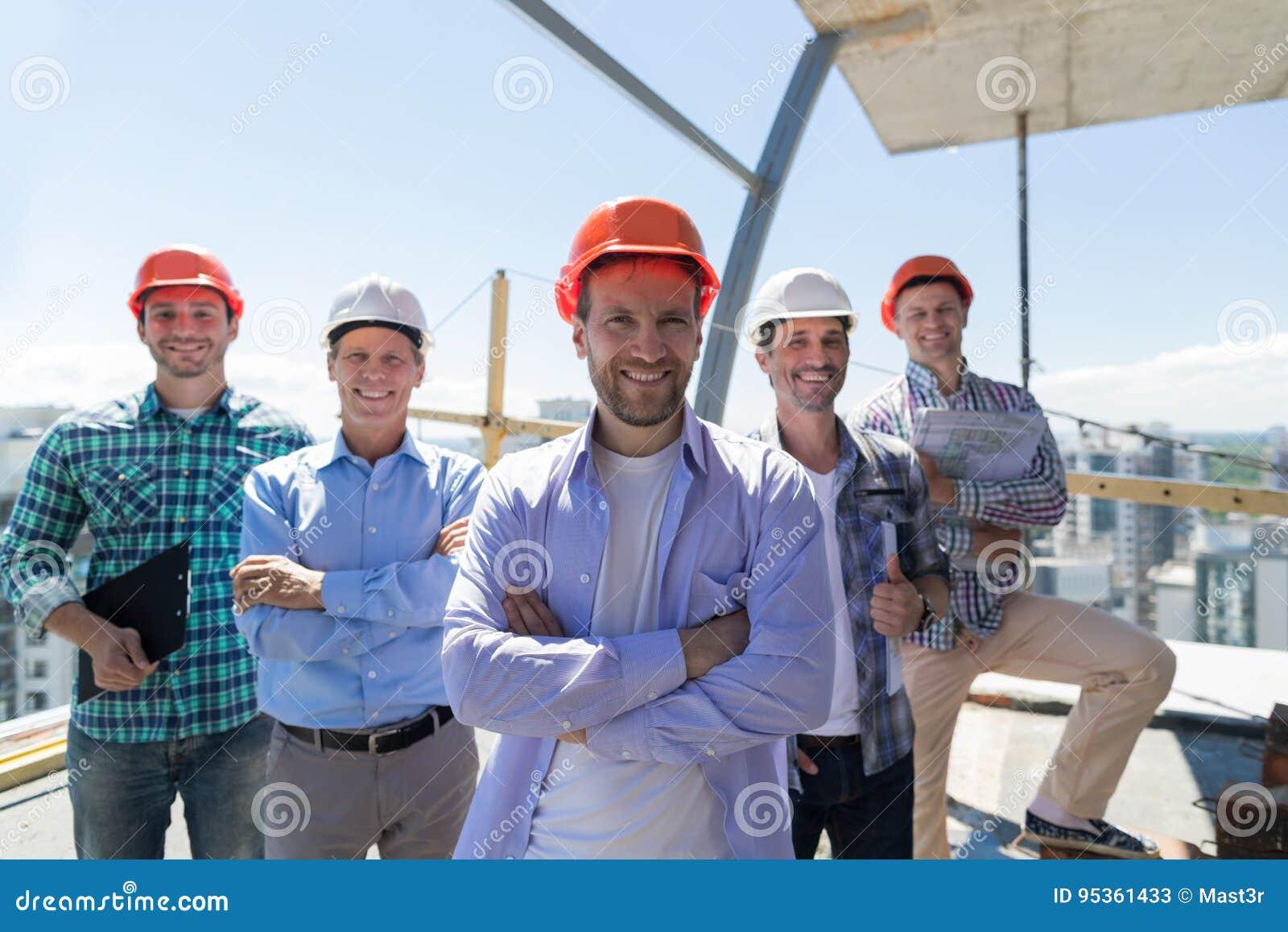 ByggmästareTeam Leader Over Group Of lärlingar på konstruktionsplatsen, lyckligt le teknikerteamworkbegrepp