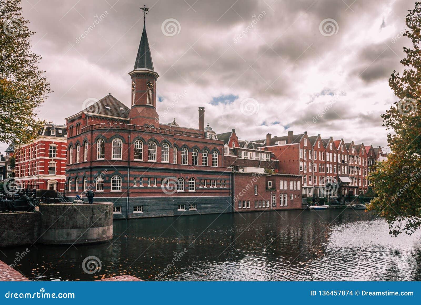Byggnad vid den Amsterdam kanalen på en lynnig dag