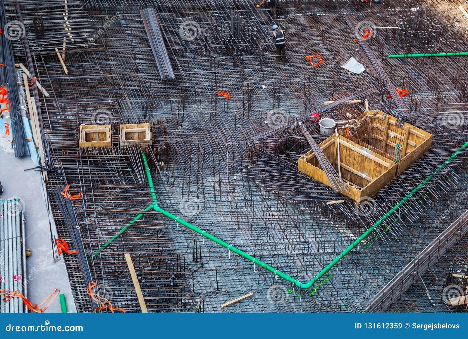 Byggnadsarbetare som fabricerar stålförstärkningstången på konstruktionsplatsen