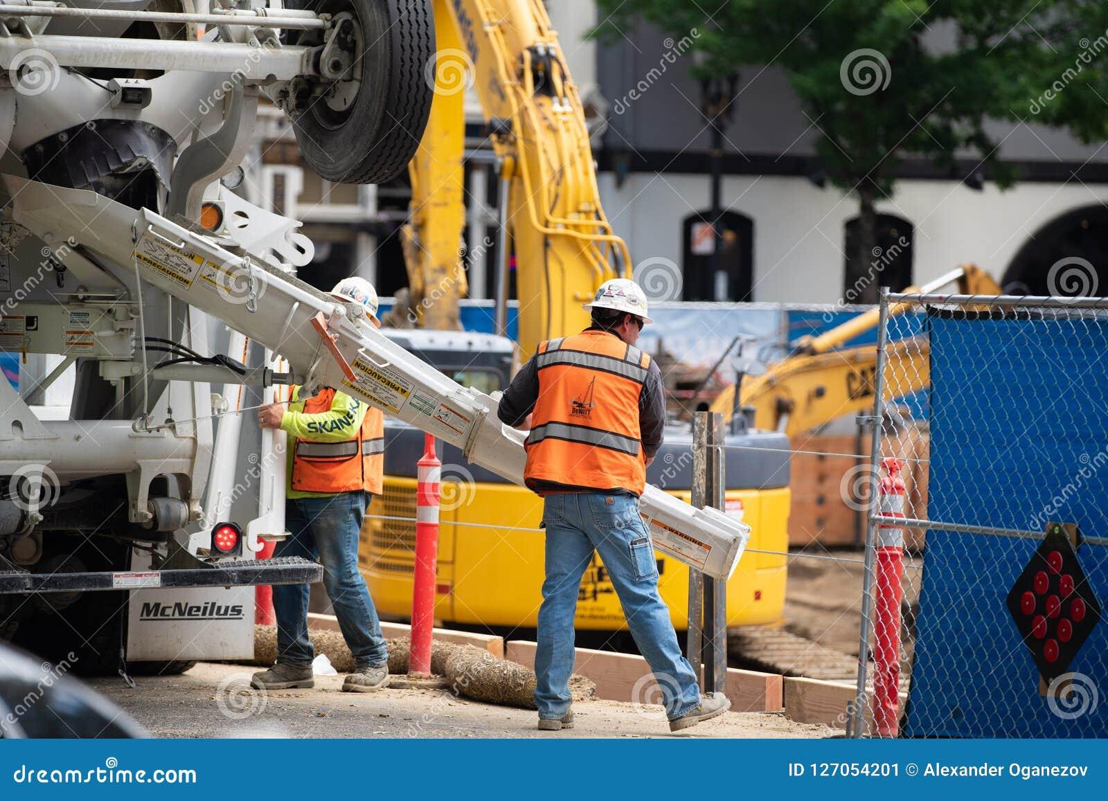 Byggnadsarbetare som häller betong