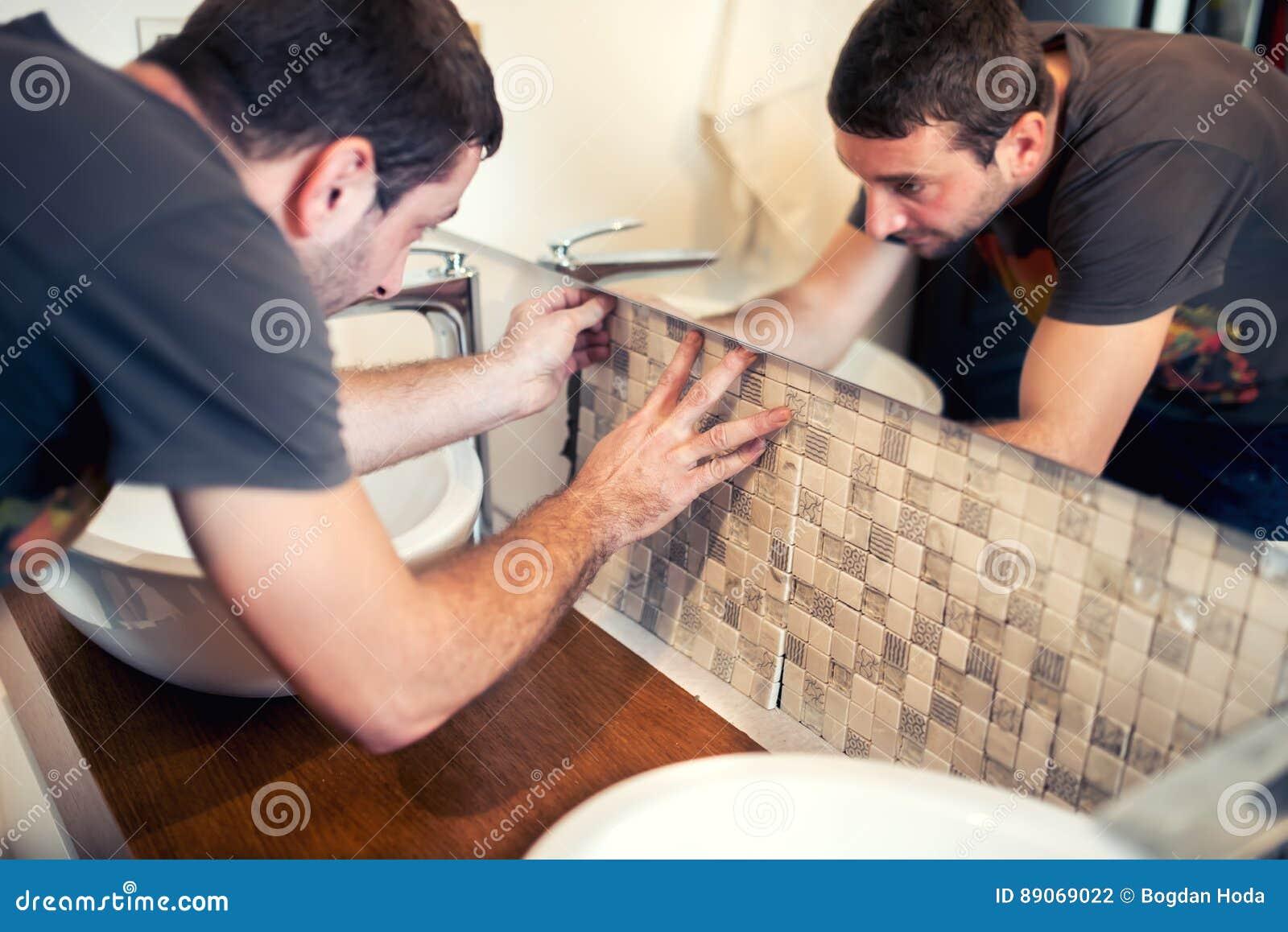 Byggnadsarbetare som lägger keramiska tegelplattor, Tiler som förlägger den keramiska väggtegelplattan i position över bindemedel