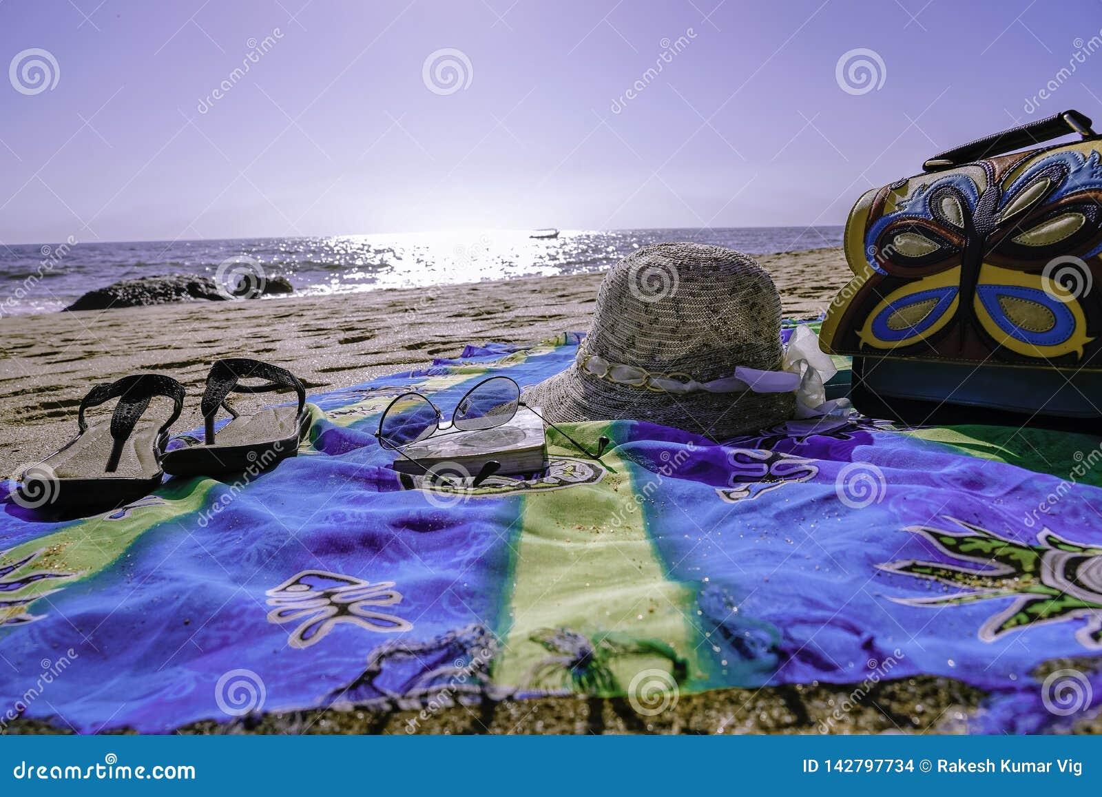 Bylte på stranden med häftklammermatarehattskyddsglasögon och en påse