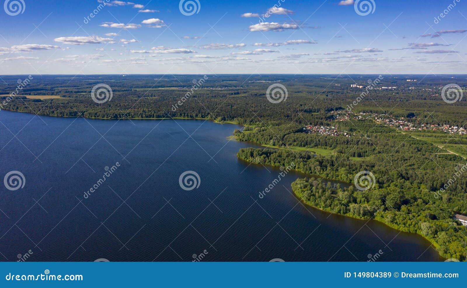 Byn i skogen nära sjön med stackmolnmoln