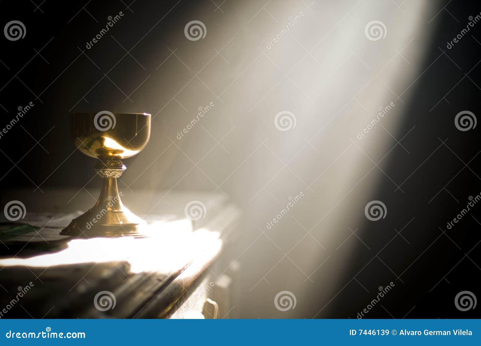 Cáliz del oro en altar con un rayo de la luz divina