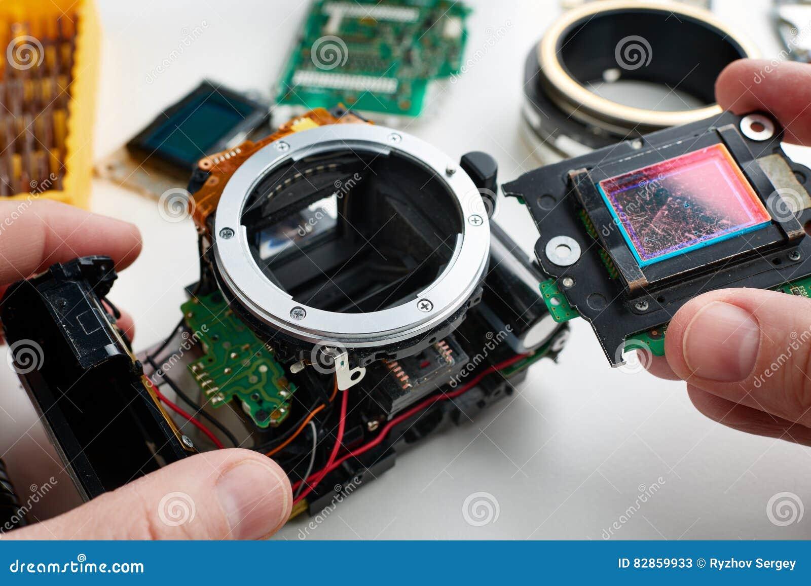 Cámara digital rasguñada vieja de SLR del sensor de la imagen en manos de servic