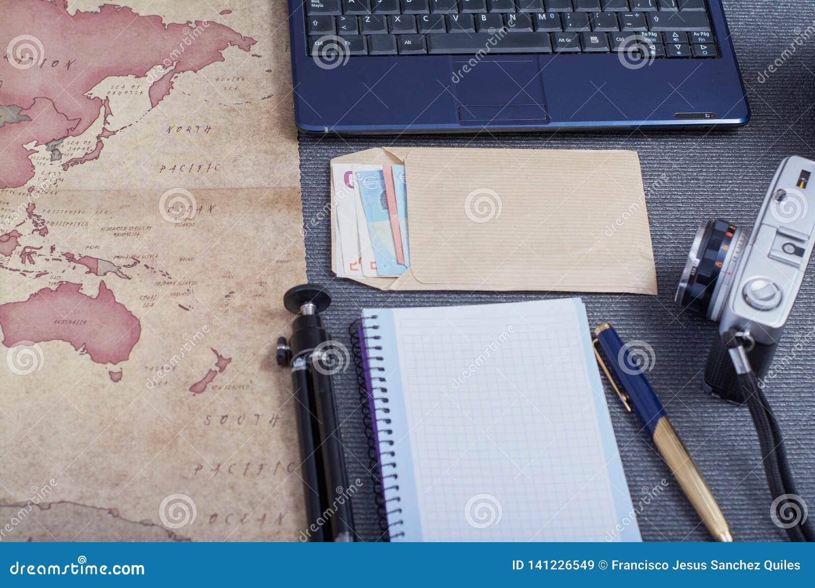 Cámara fotográfica del vintage al lado de un mapa, de un trípode y de un sobre del dinero en los euros que preparan un viaje