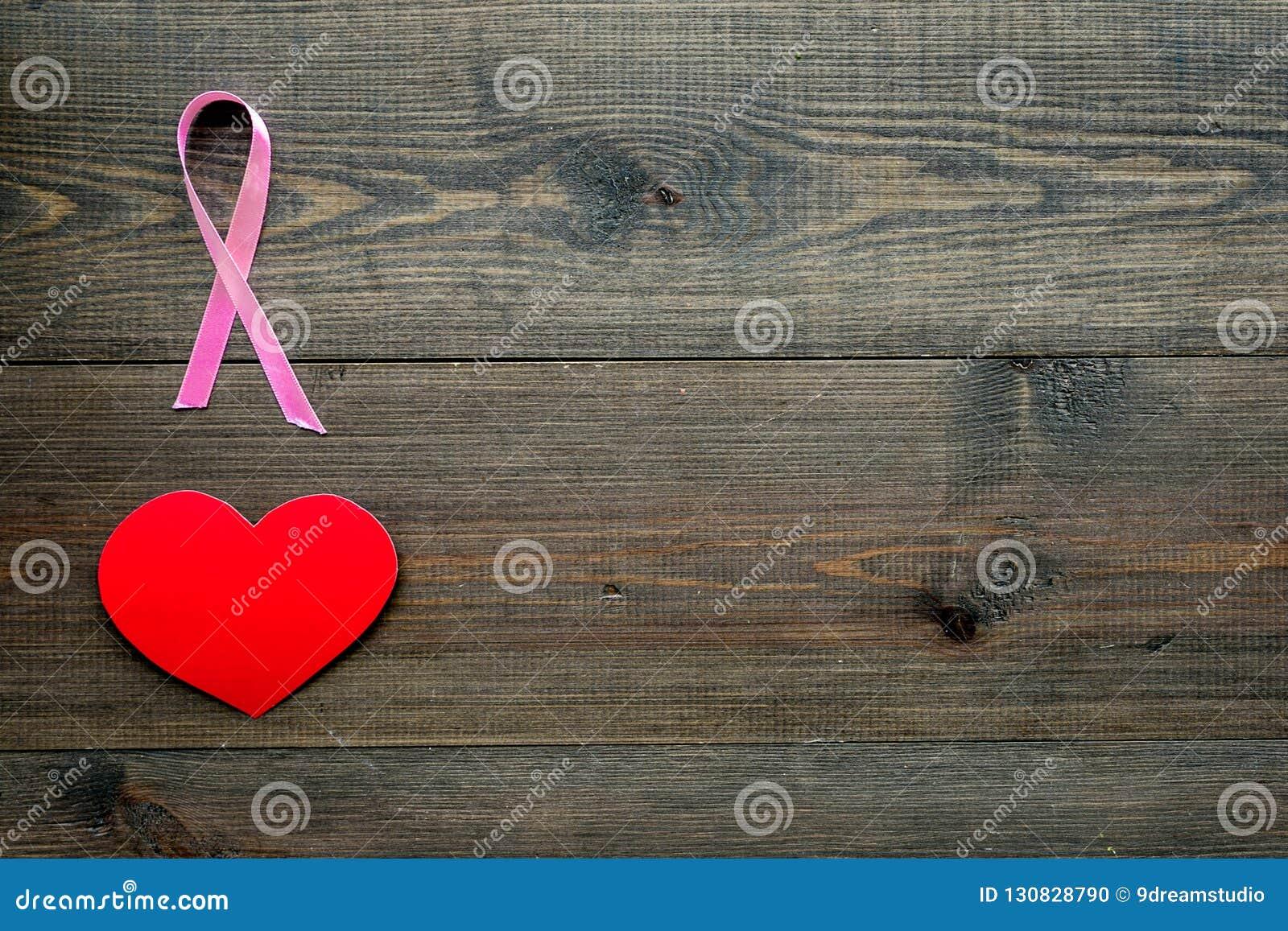 Cáncer de pecho Concepto del Mammalogy Cinta rosada simbólica cerca de la muestra del corazón en espacio de madera oscuro de la c