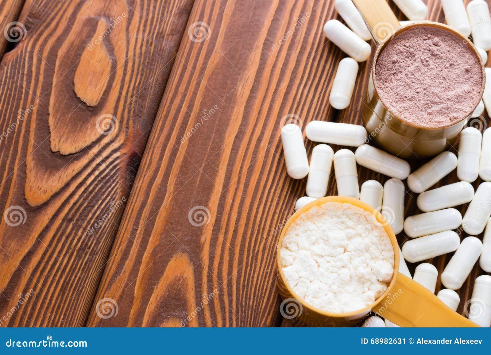 Cápsulas de cucharas dosificadoras de la creatina y de la proteína