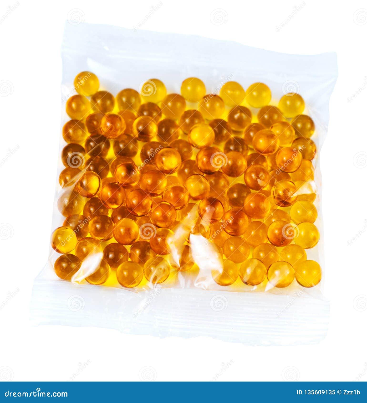 Cápsulas esféricas anaranjadas de la bola de aceite de pescado en la bolsa de plástico aislada en el fondo blanco