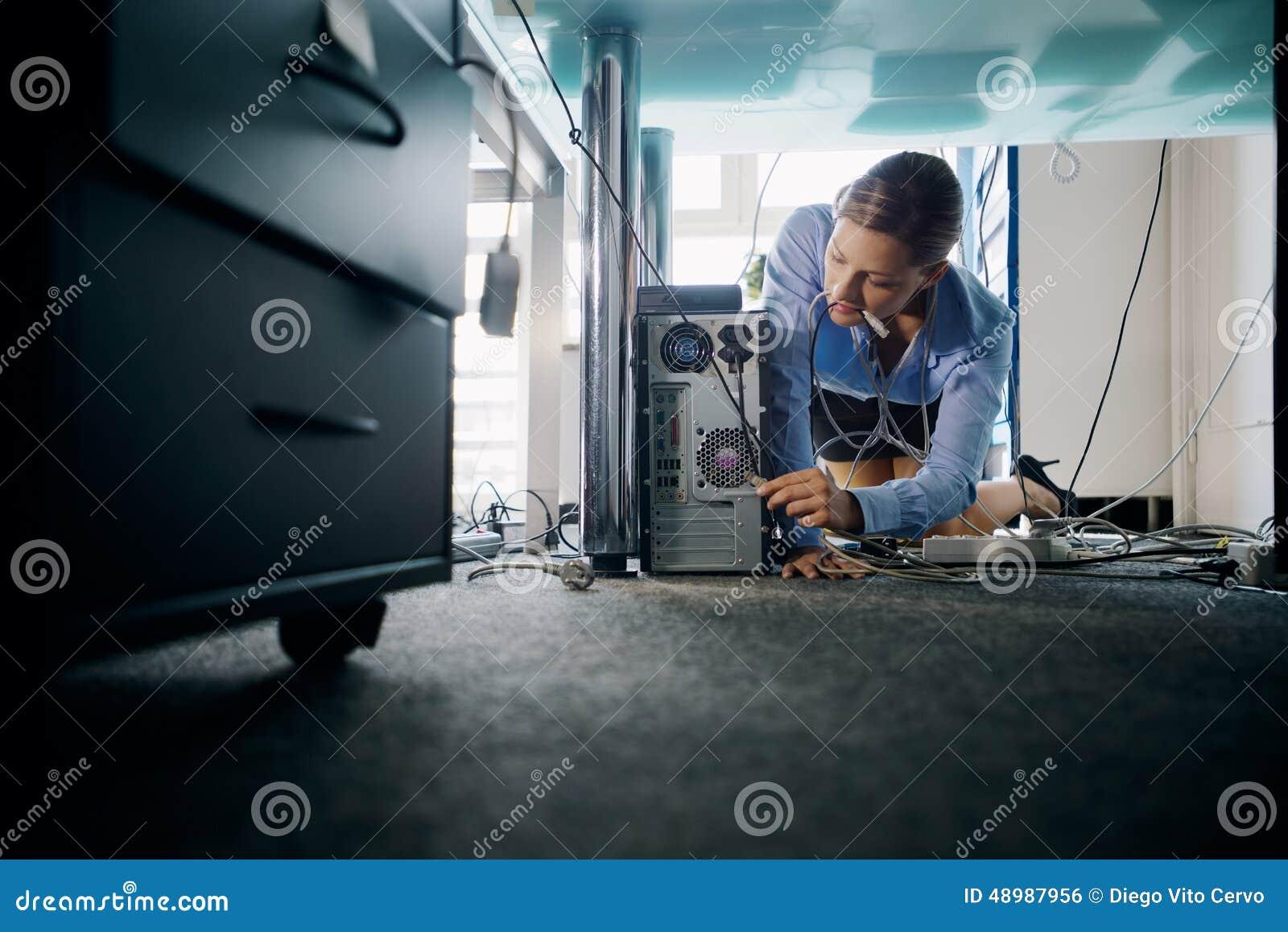 Câbles se reliants de jeune secrétaire au pc dans le bureau photo
