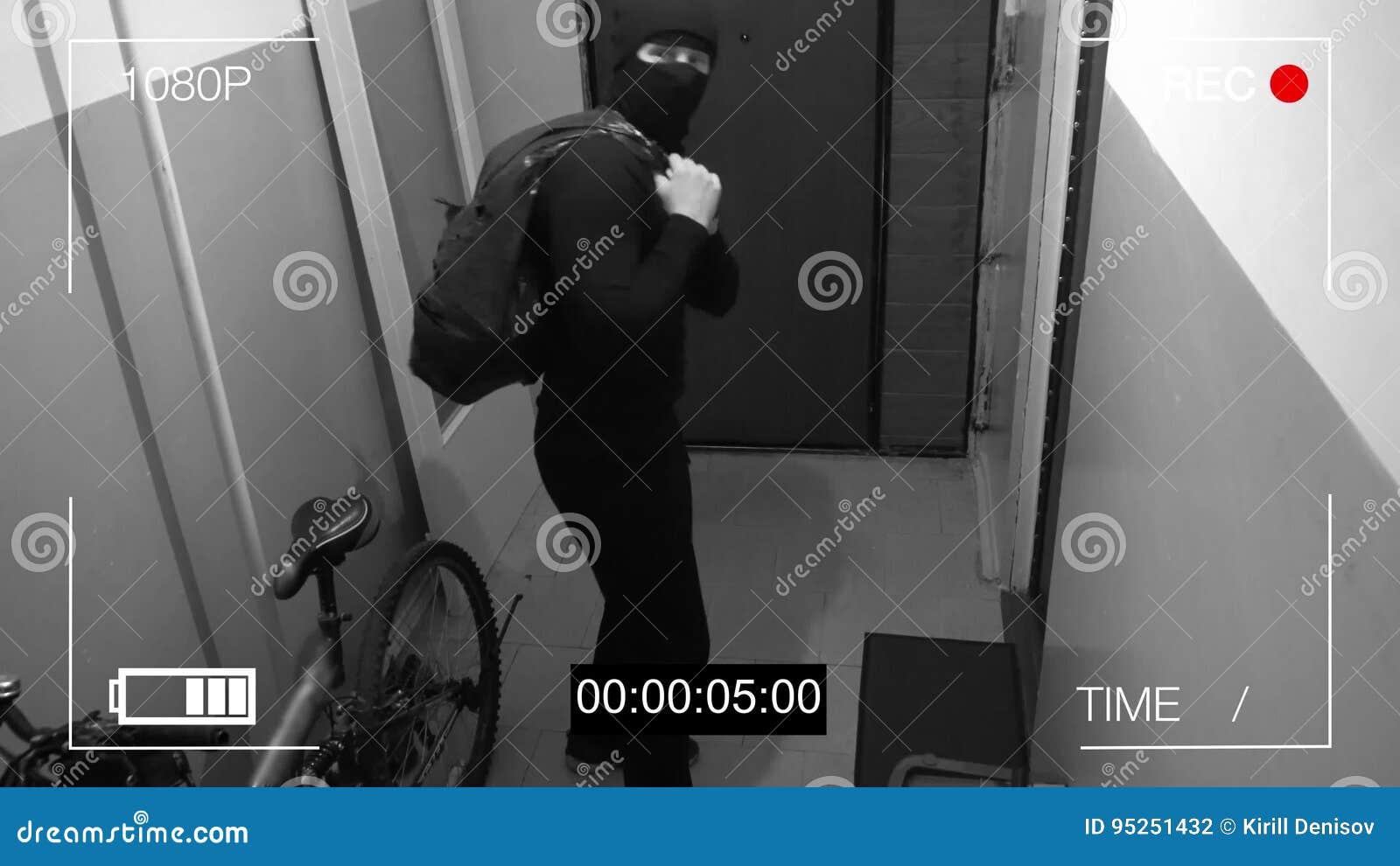 A câmara de vigilância travou o ladrão em uma máscara que foge com um saco da pilhagem, mostra à câmera o dedo médio