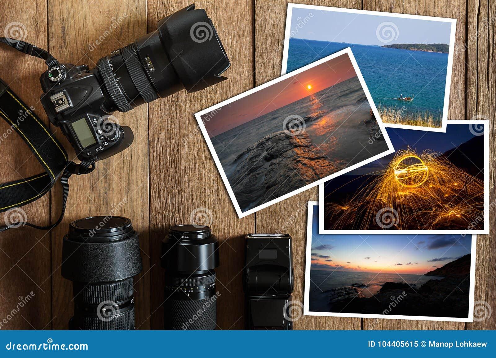 Câmara digital, lente, flash e pilha de DSLR de fotos no fundo de madeira do grunge do vintage