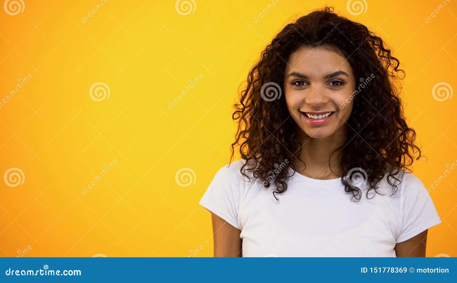 Câmera de sorriso da mulher afro-americana contente, estudante fêmea, bem-estar, feminilidade