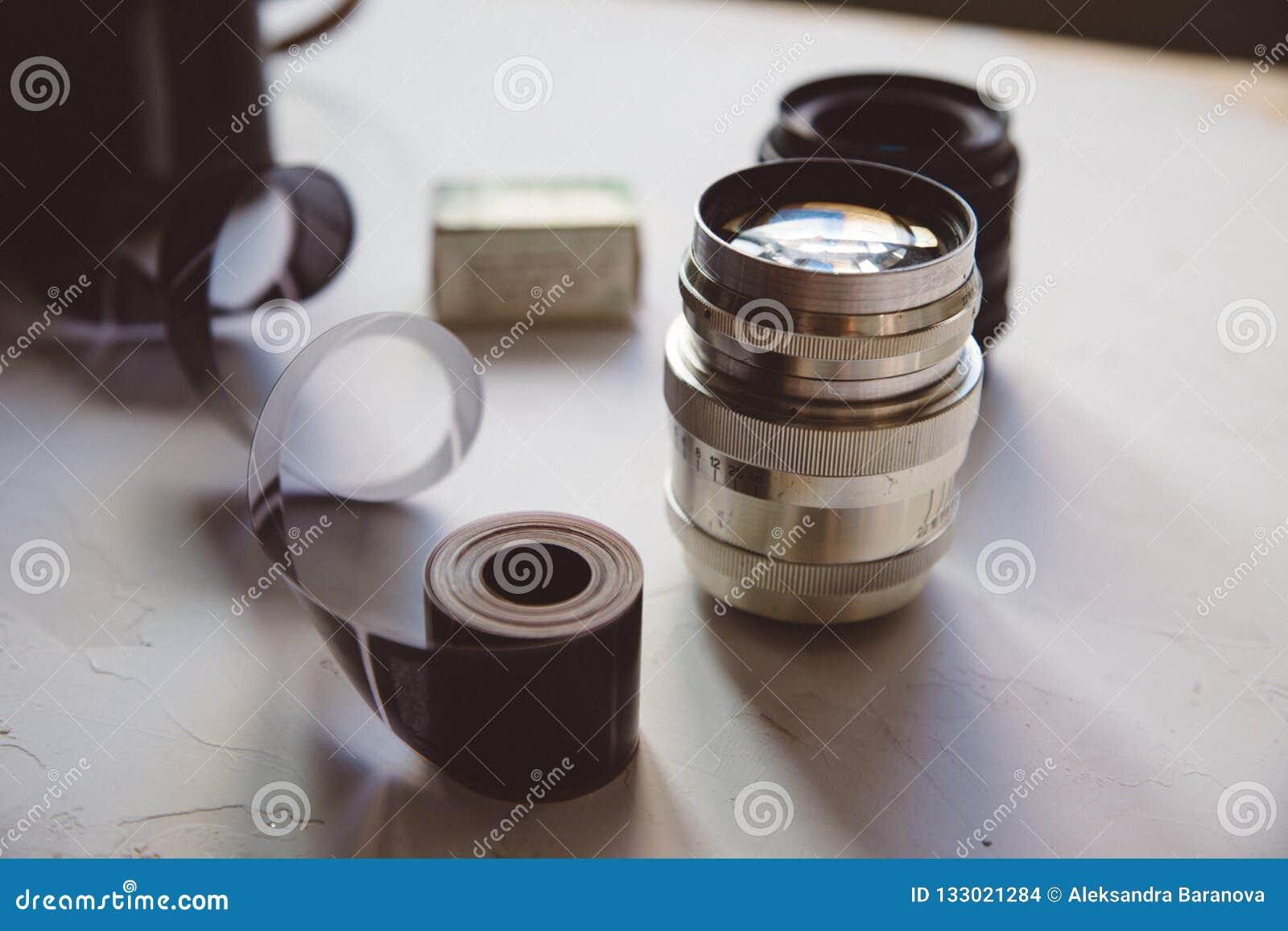 Câmera do vintage, filme, lentes retros na tabela branca, espaço da cópia