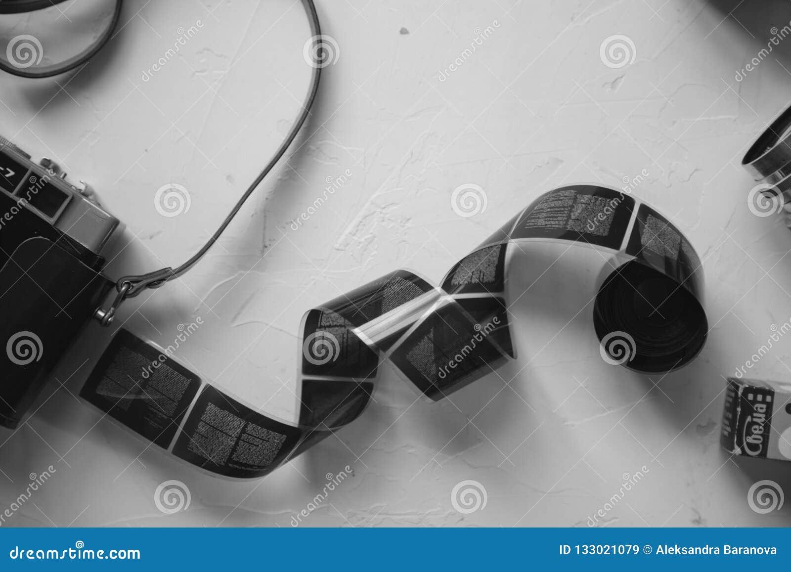 Câmera do vintage, filme, lentes retros na tabela branca, espaço da cópia, preto e branco