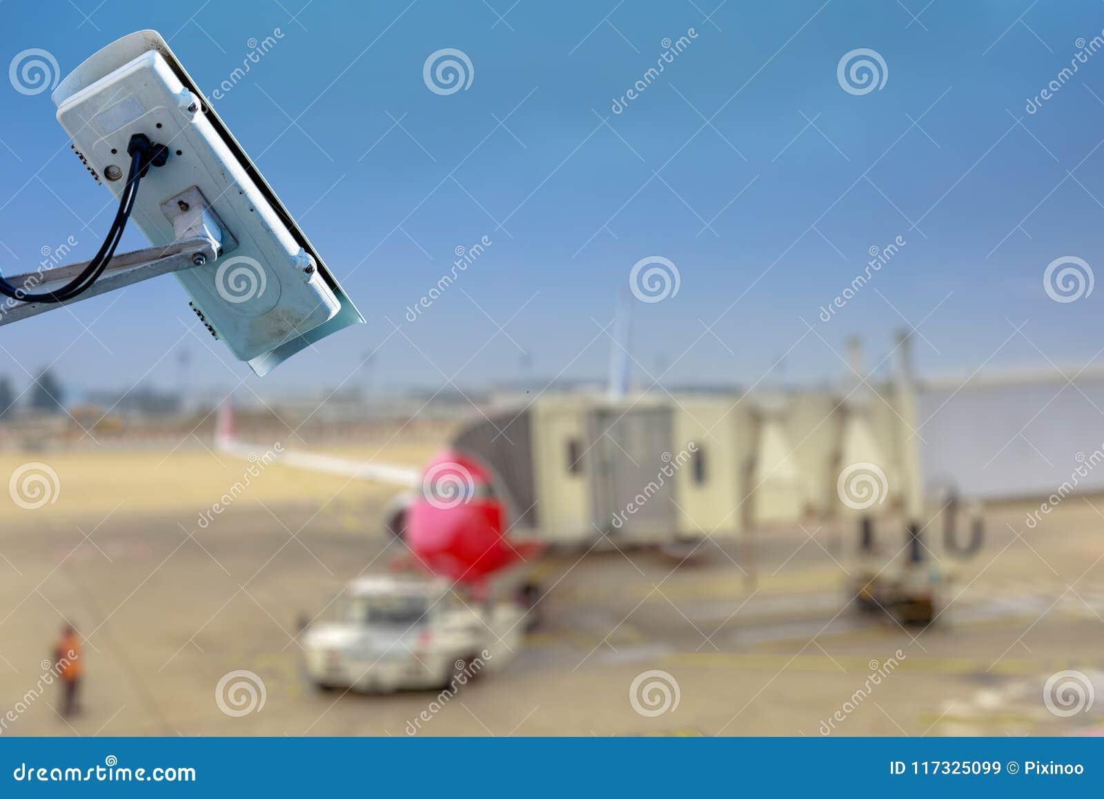Câmera ou sistema de vigilância do CCTV da segurança com alcatrão do aeroporto no fundo obscuro