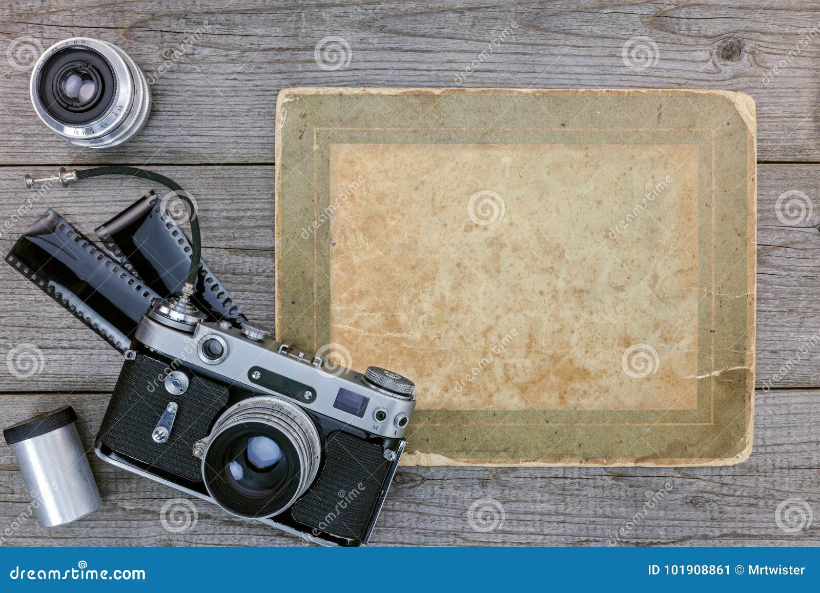 Câmera retro, filme negativo, lentes no fundo de madeira da tabela