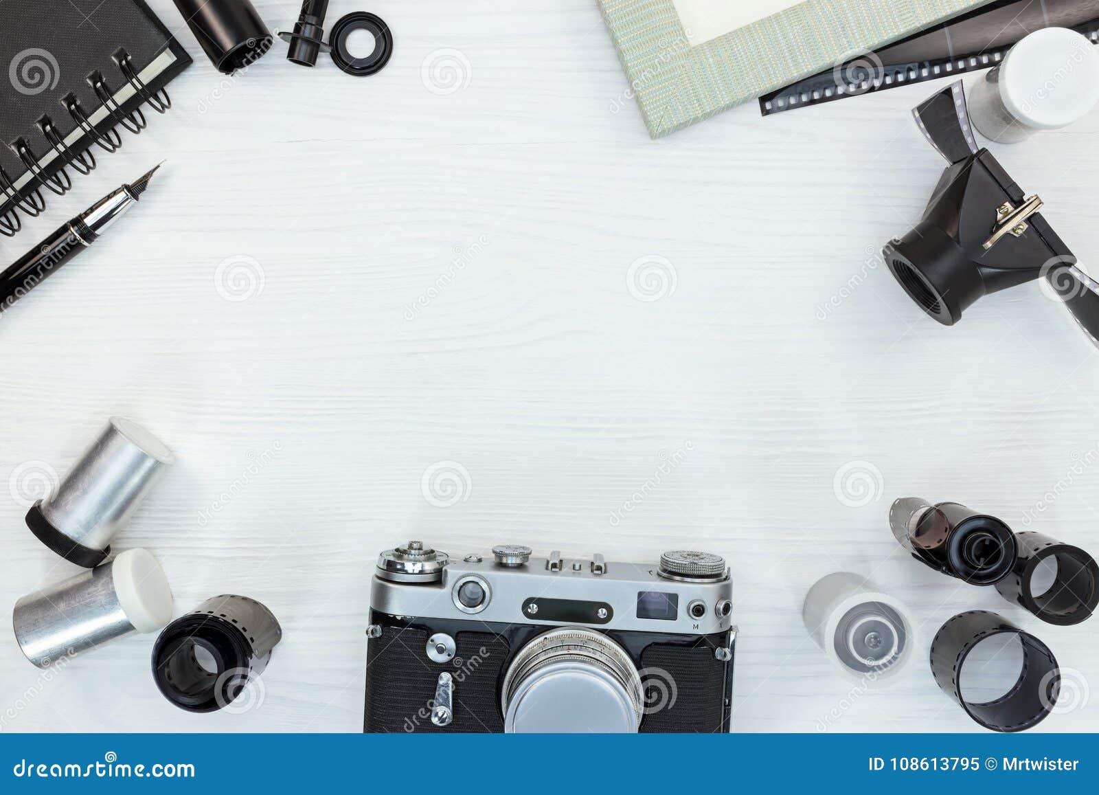Câmera retro, rolos de filme, lente, quadro vazio da foto no woode branco