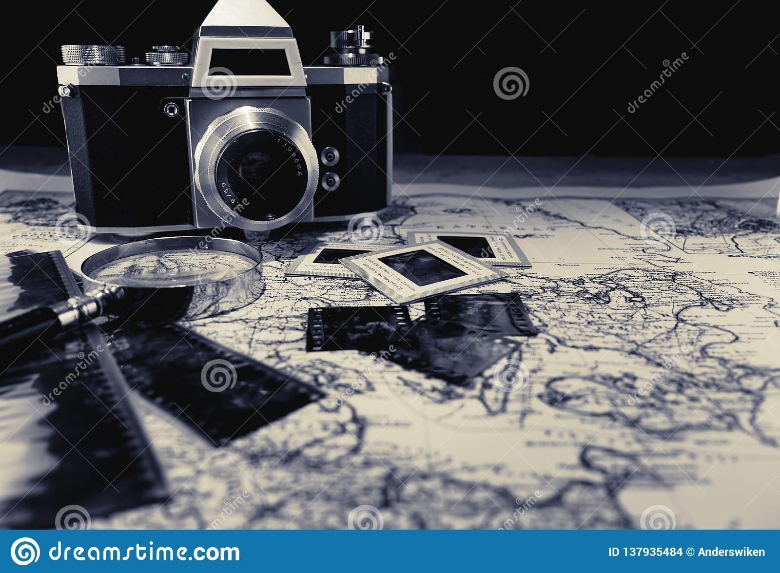Câmera velha do vintage no mapa com negativos