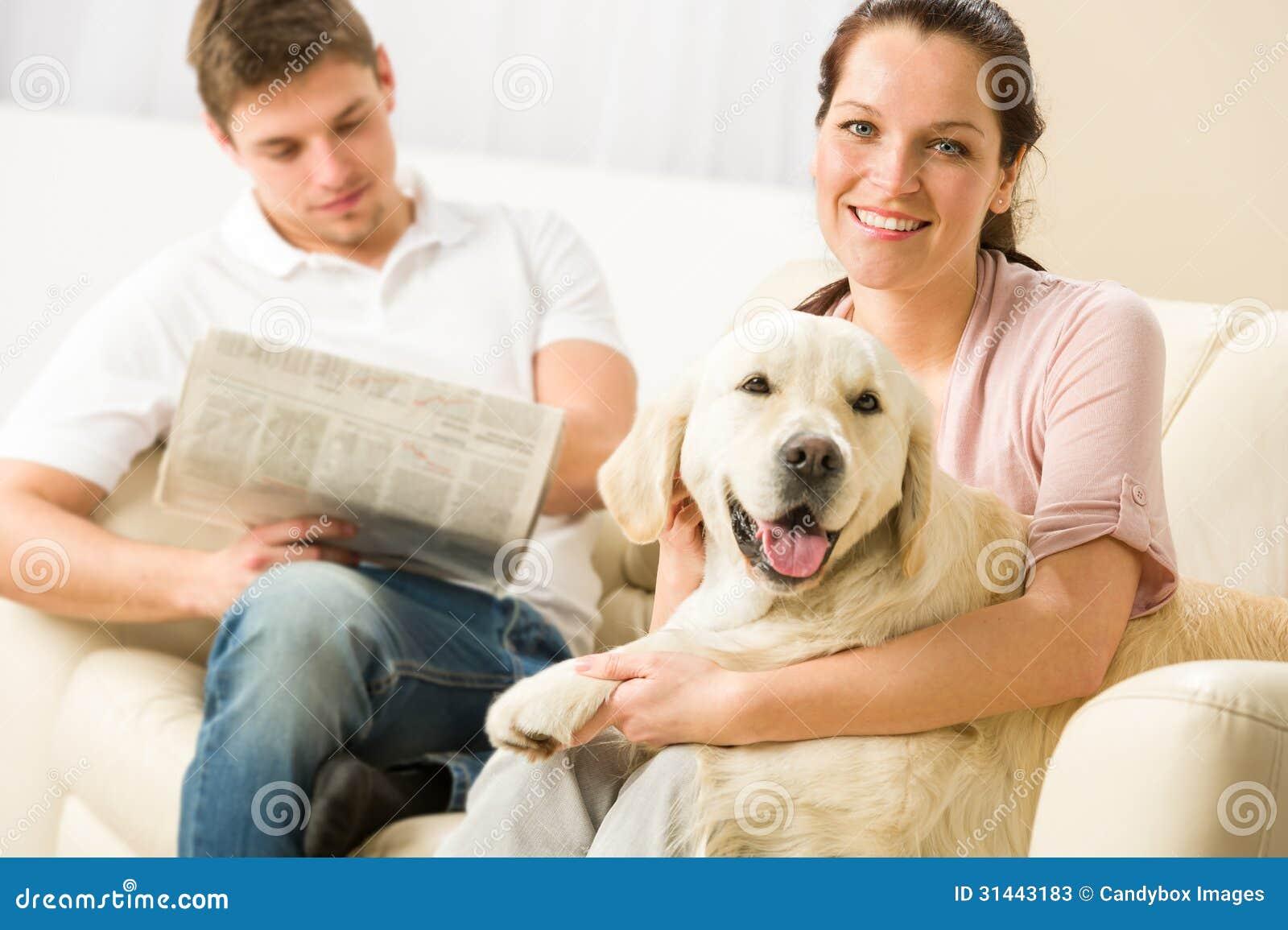 Cão alegre de descanso do assento e das trocas de carícias dos pares