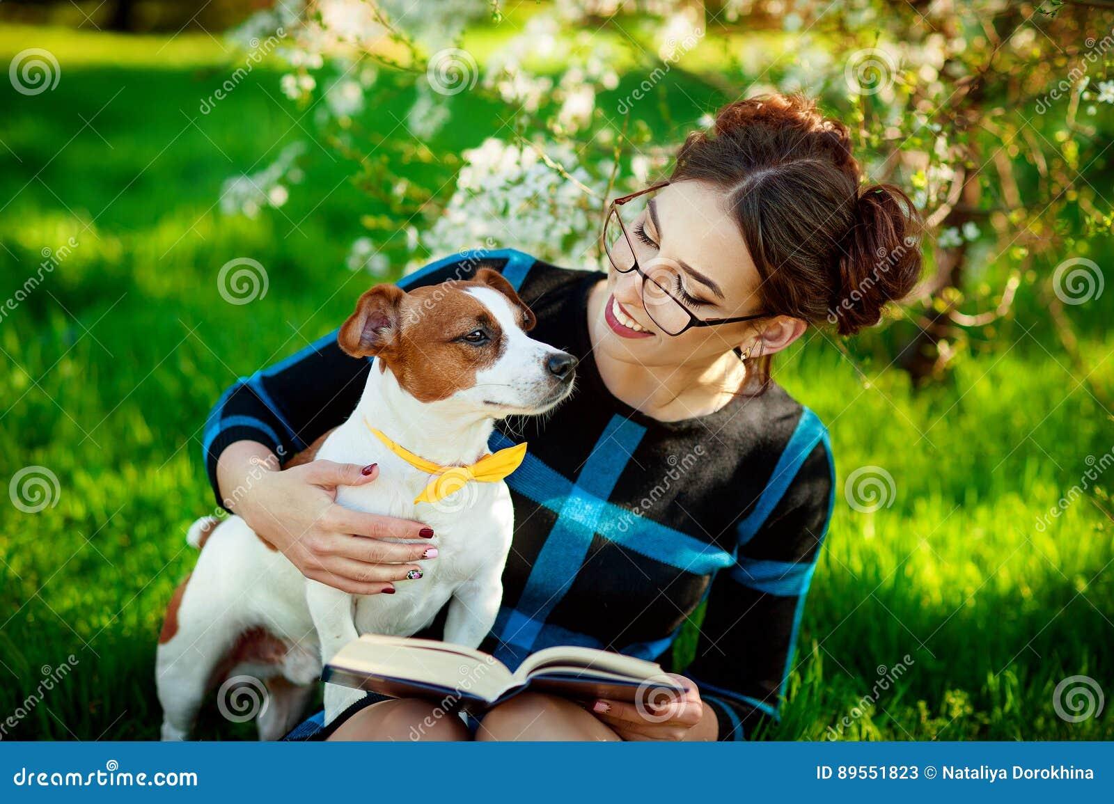 Cão de Jack Russell Terrier com a mulher do proprietário que joga na primavera fora Conceito moderno do estilo de vida da juventu