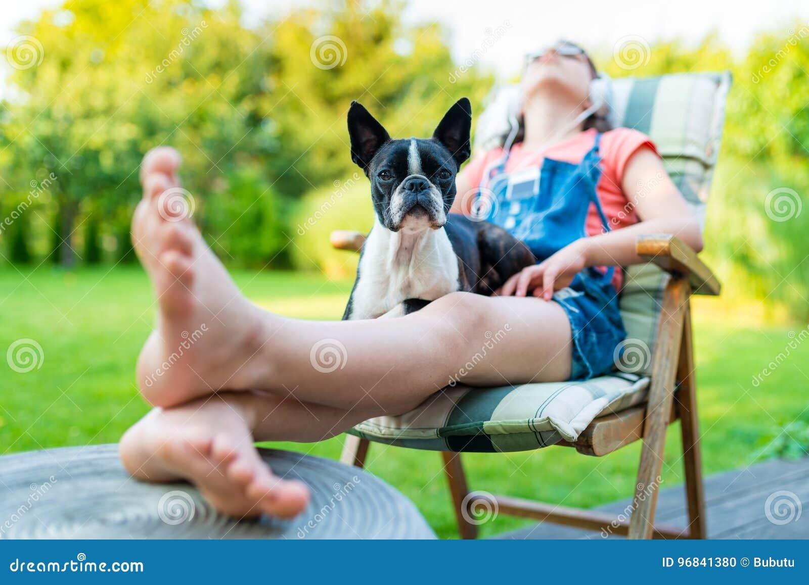 Cão e adolescente que descansam no jardim