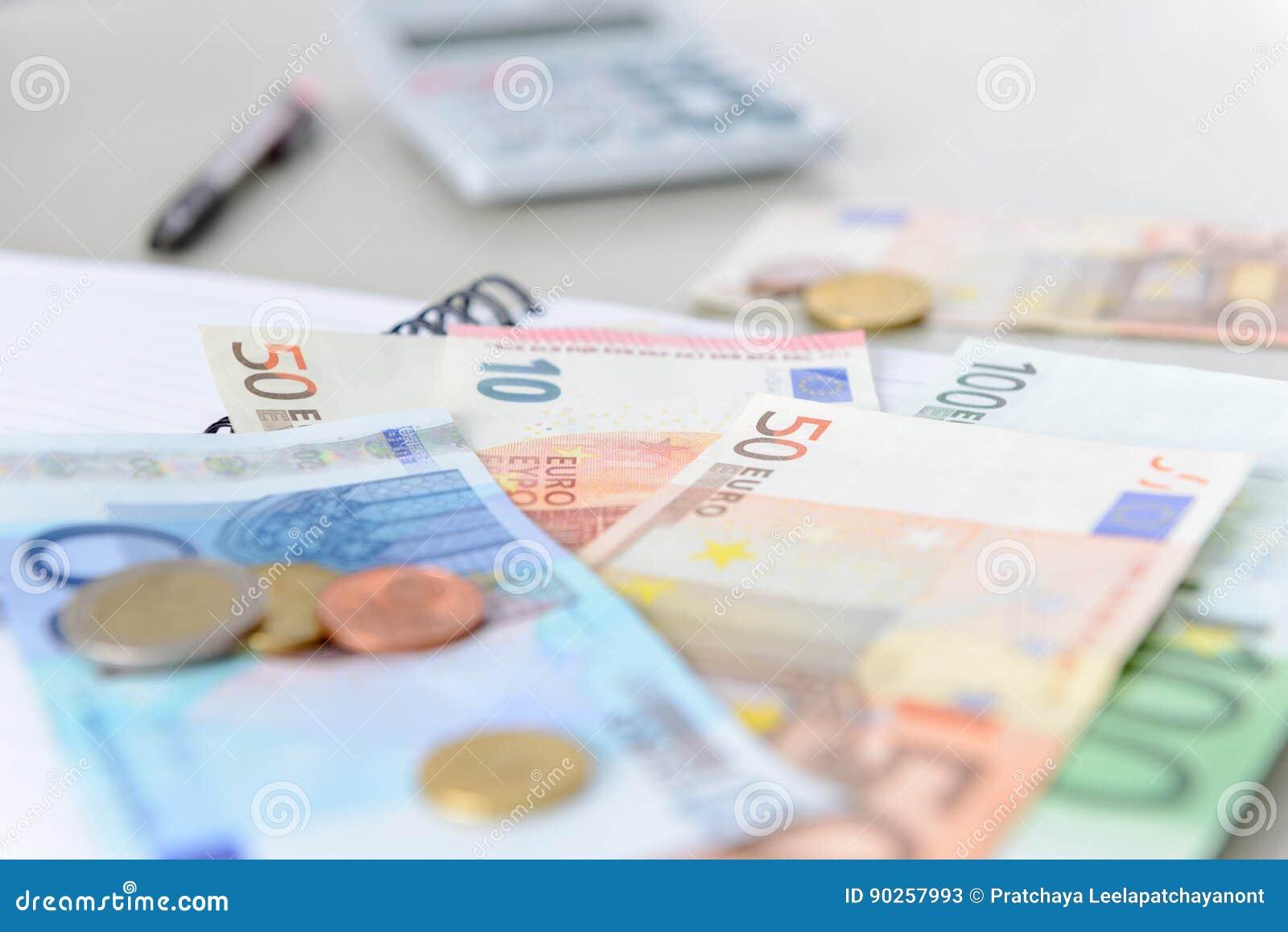 Cédulas e moedas do dinheiro do Euro que contam com calculadora, caderno e pena