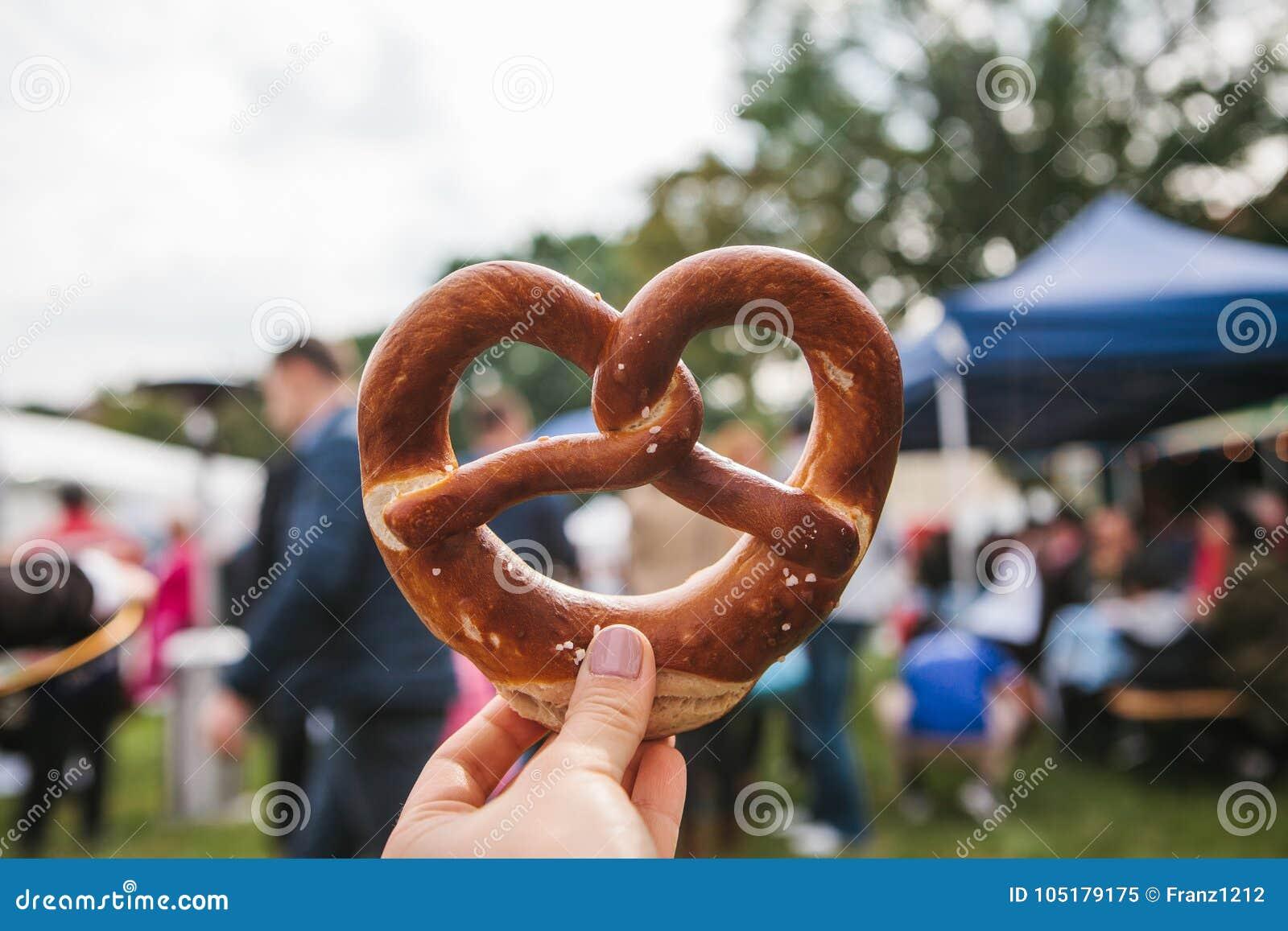 Célébration du festival allemand célèbre Oktoberfest de bière que la personne se tient dans sa main un bretzel traditionnel a app
