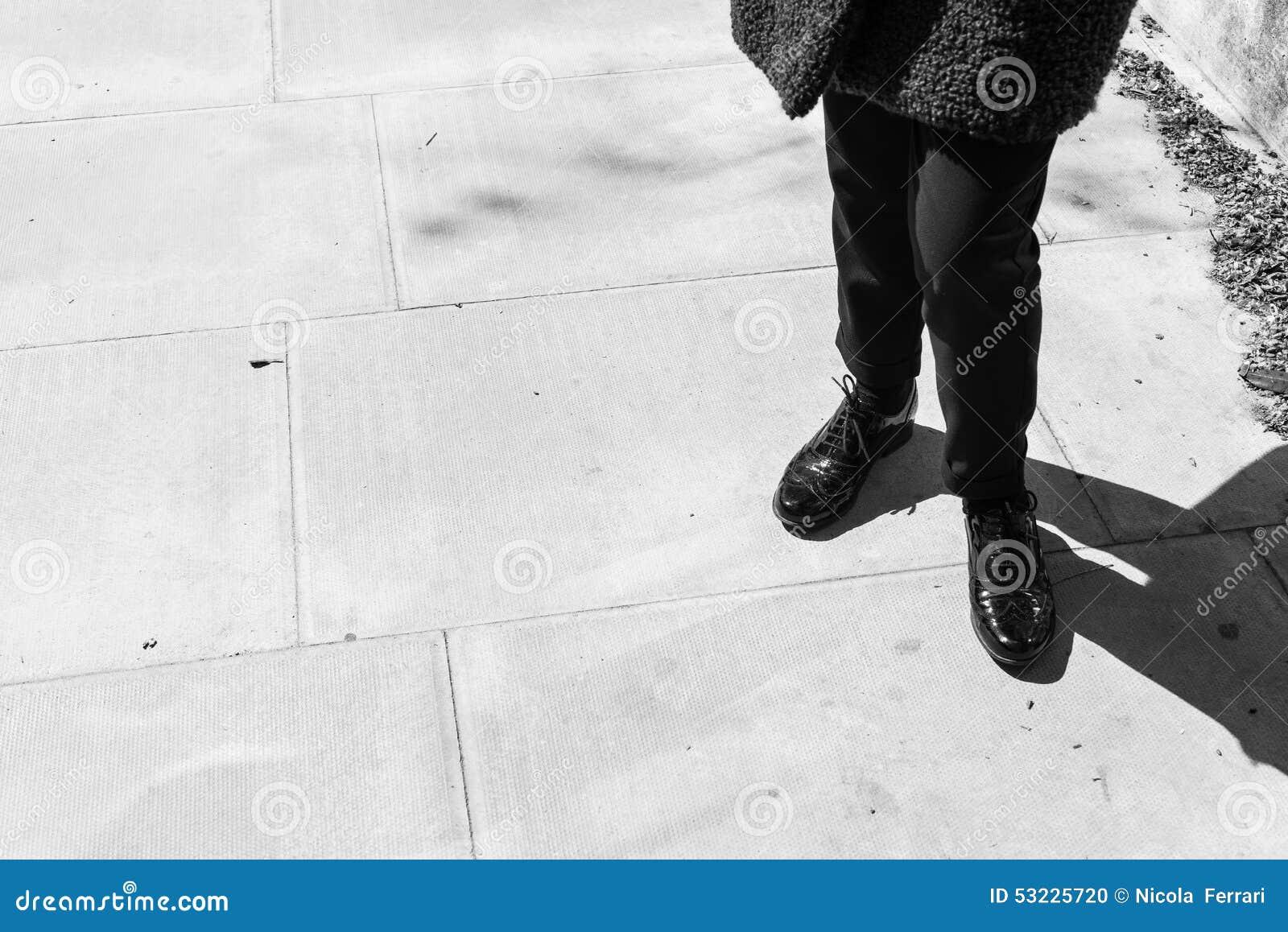 Céntrese en las piernas de la mujer que llevan abarcas del cuero del negro del estilo de Londres