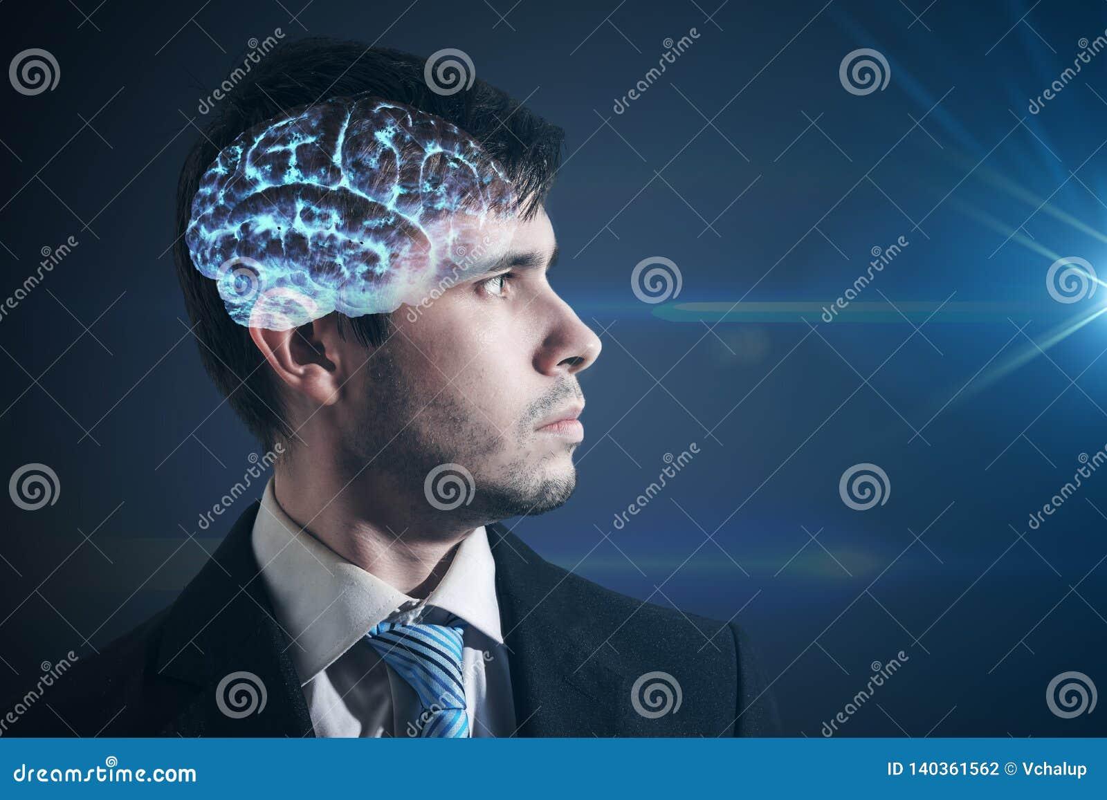 Cérebro de incandescência dentro da cabeça do homem O homem de negócios está olhando na luz