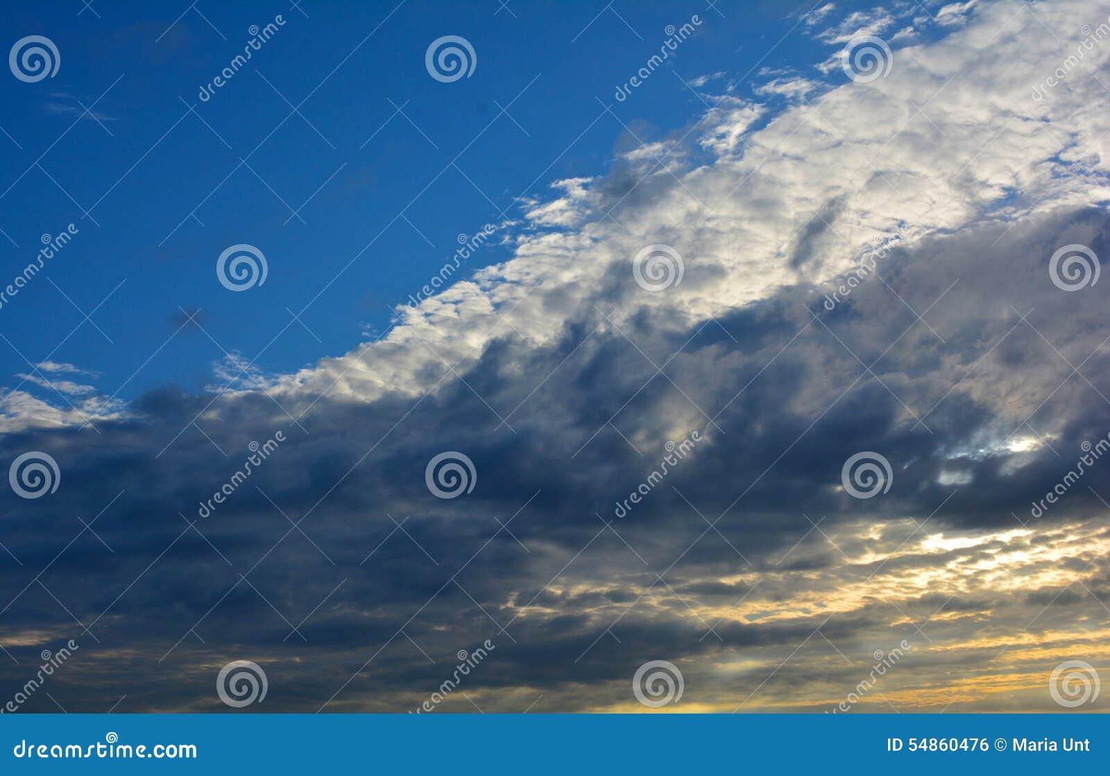 Céu azul brilhante com as nuvens brancas no por do sol, Norfolk, Reino Unido