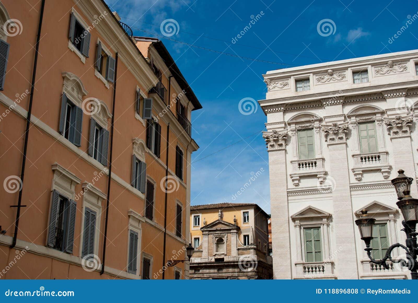 Céu azul e construção amarela em Roma próximo de Fontana di Trevi na rua do Trevi, fevereiro