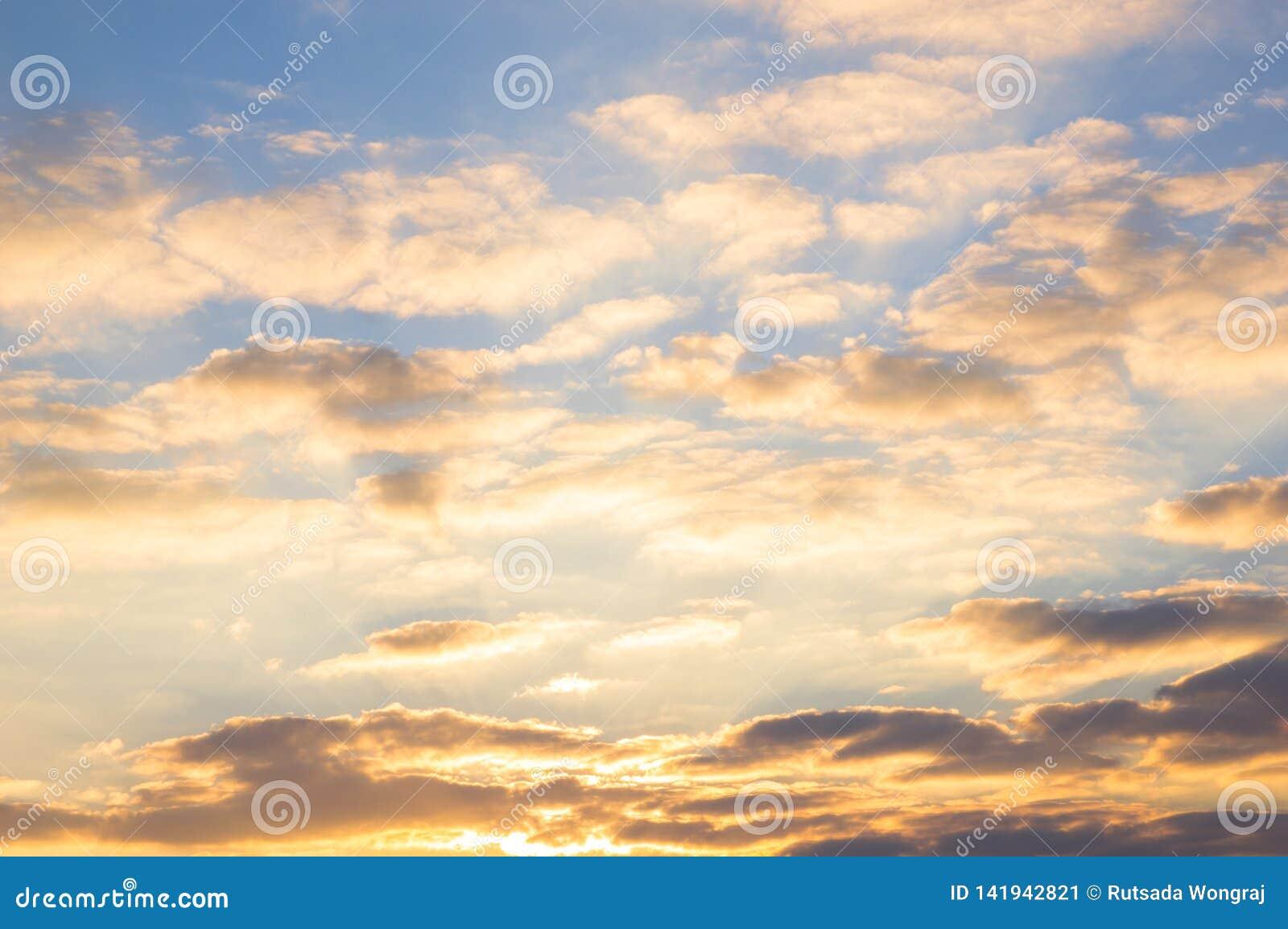 Céu azul e nuvens douradas no nascer do sol bonito