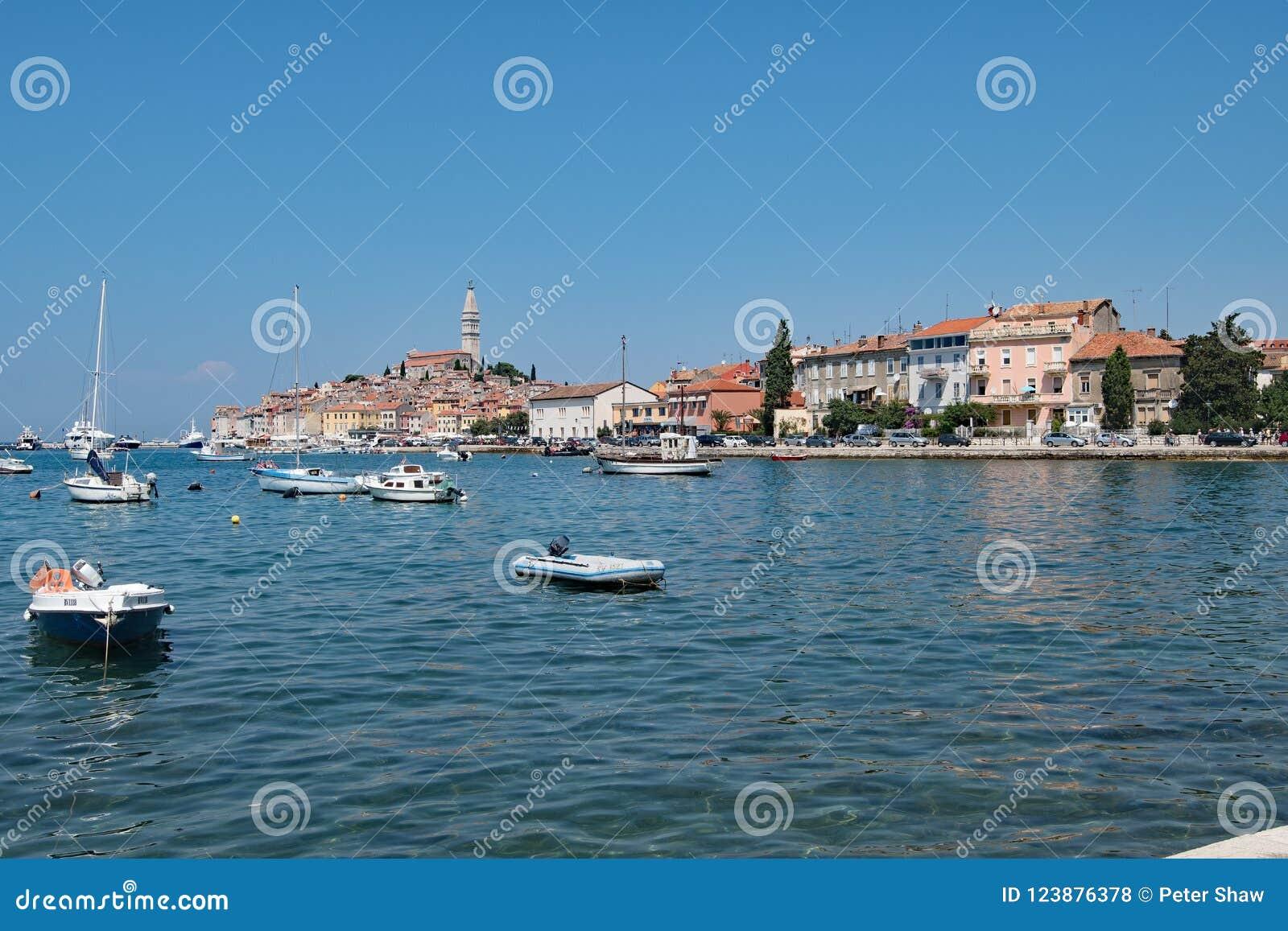 Céu azul que pensa no porto croata de Rovinj, um porto de pesca na costa oeste da Croácia