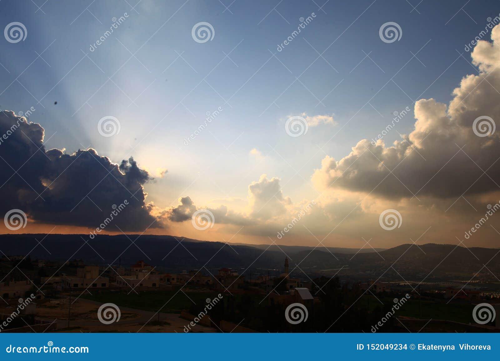 Céu do por do sol com as nuvens sobre a cidade árabe