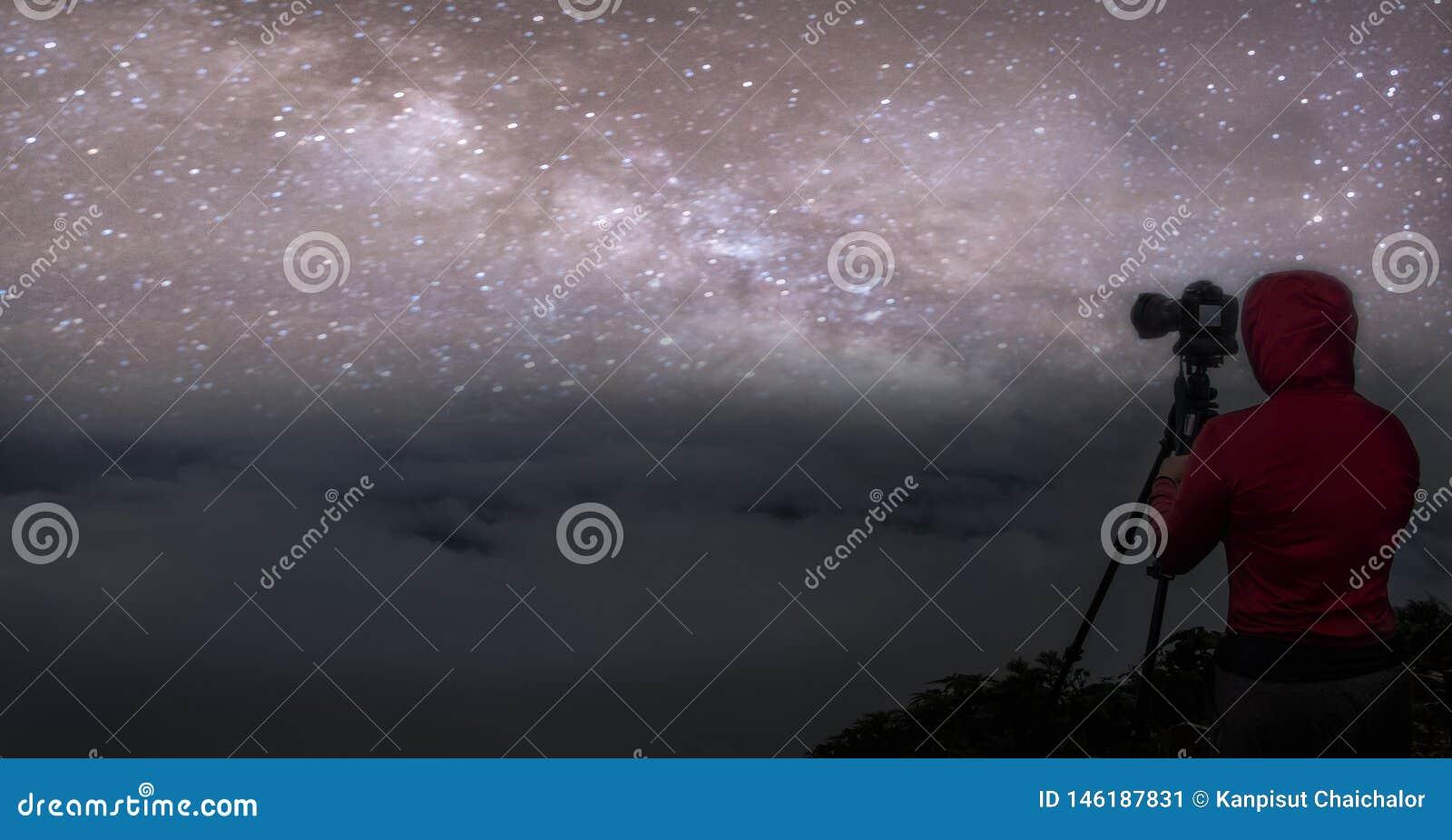 Céu noturno colorido do panorama com estrelas e silhueta de um homem ereto na pedra Via L?tea azul com o homem na montanha