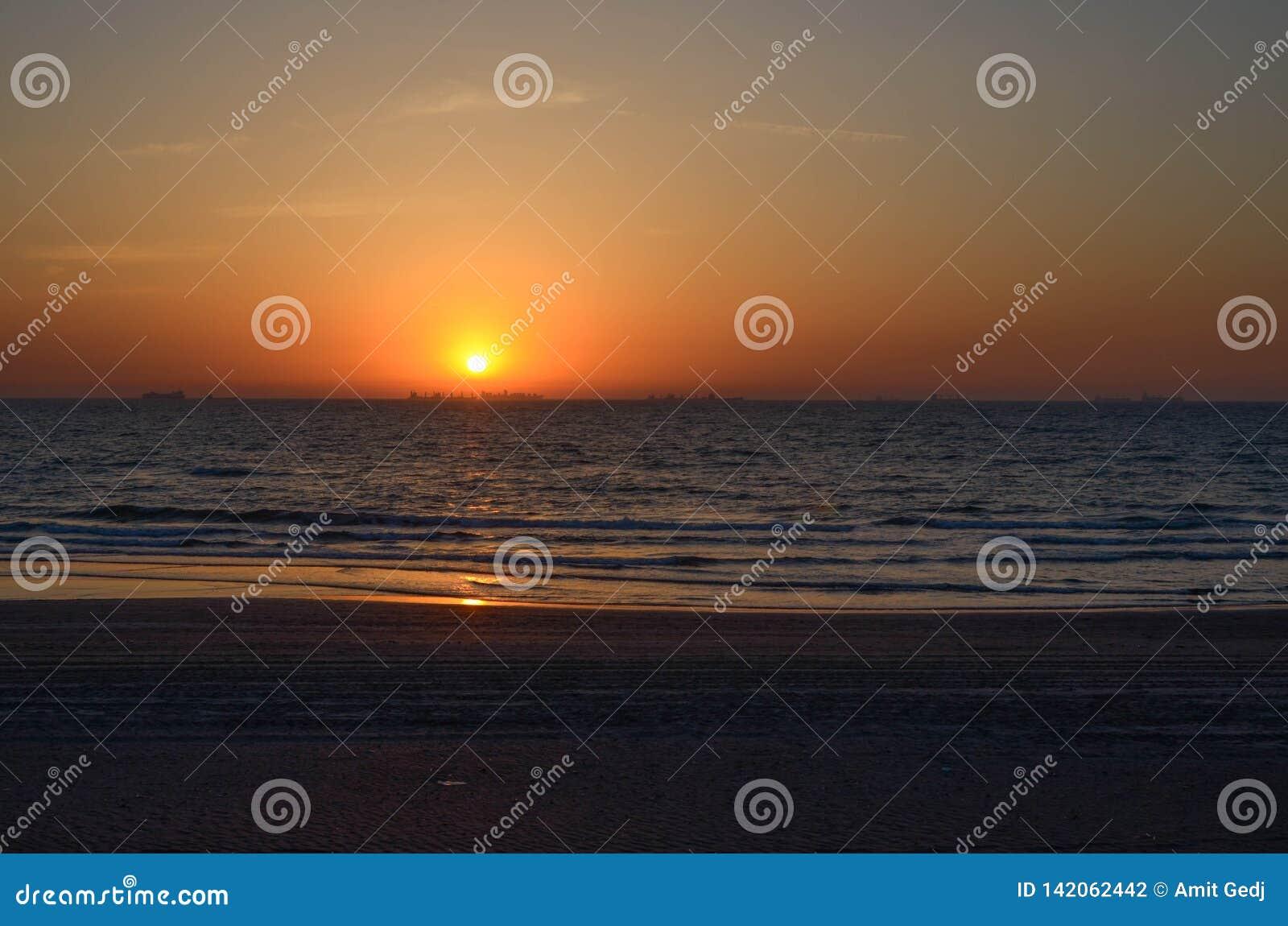 Céu vermelho e uma praia