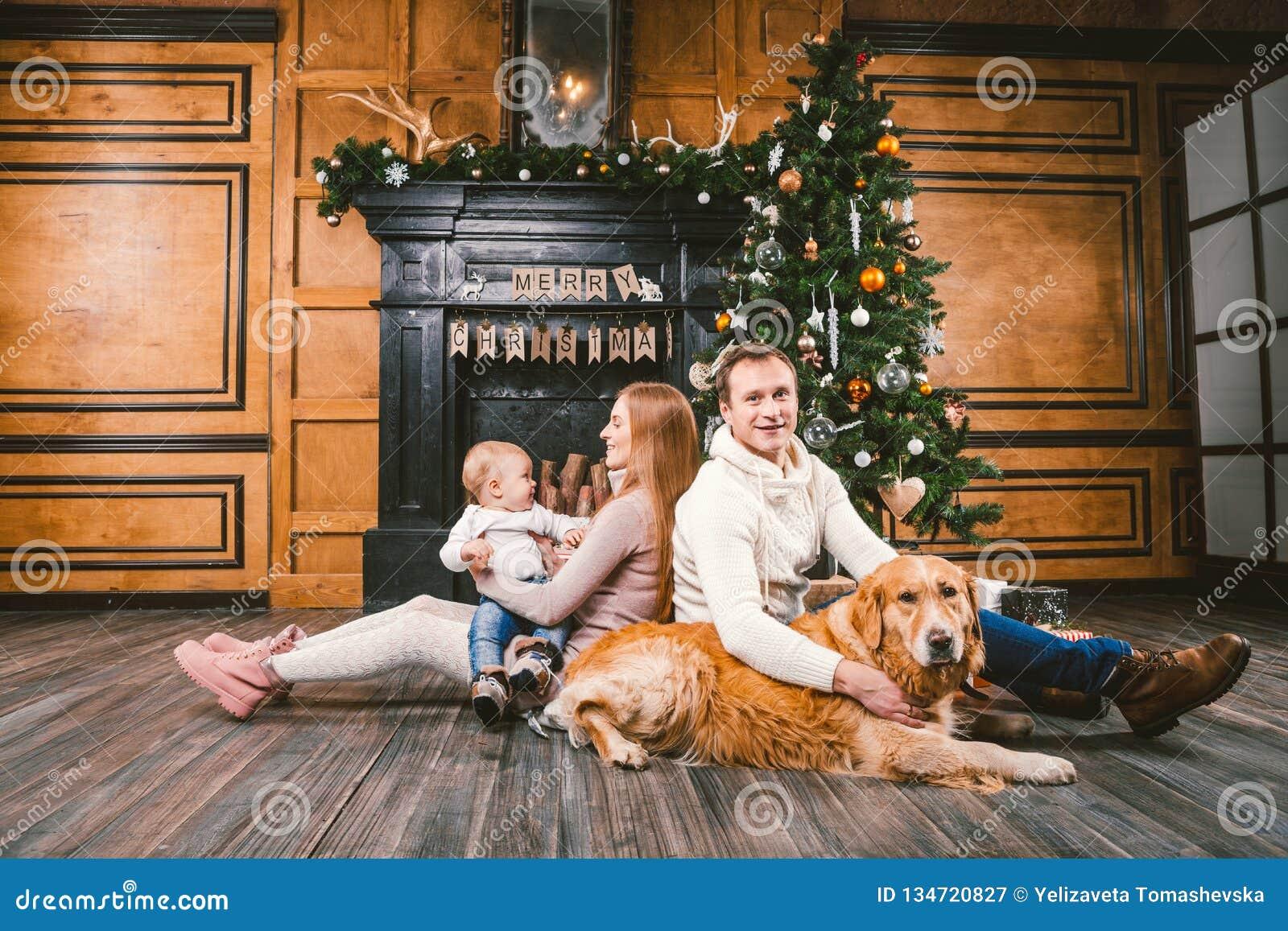 Círculo familiar de la Navidad del tema y del Año Nuevo Familia caucásica joven con el golden retriever de 1 año de Labrador de l