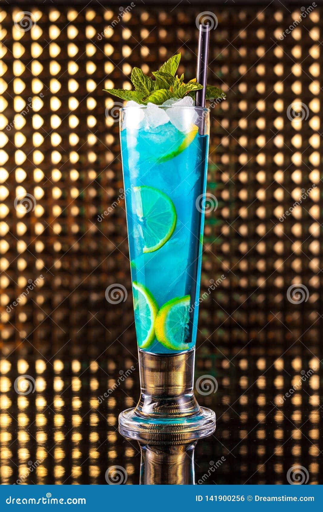 Cóctel azul claro de la baya con el limón en alto