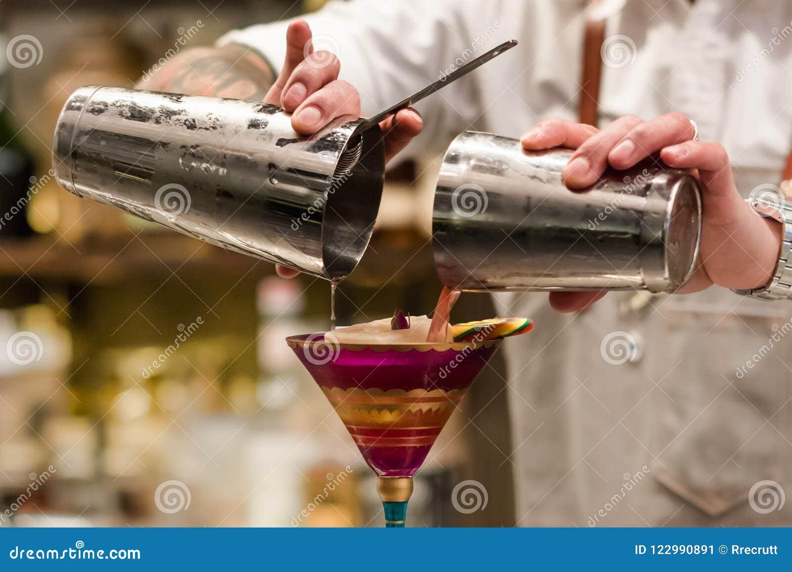 Cóctel de colada del camarero profesional de la coctelera en el vidrio Camarero que se sostiene en herramienta del cóctel de las
