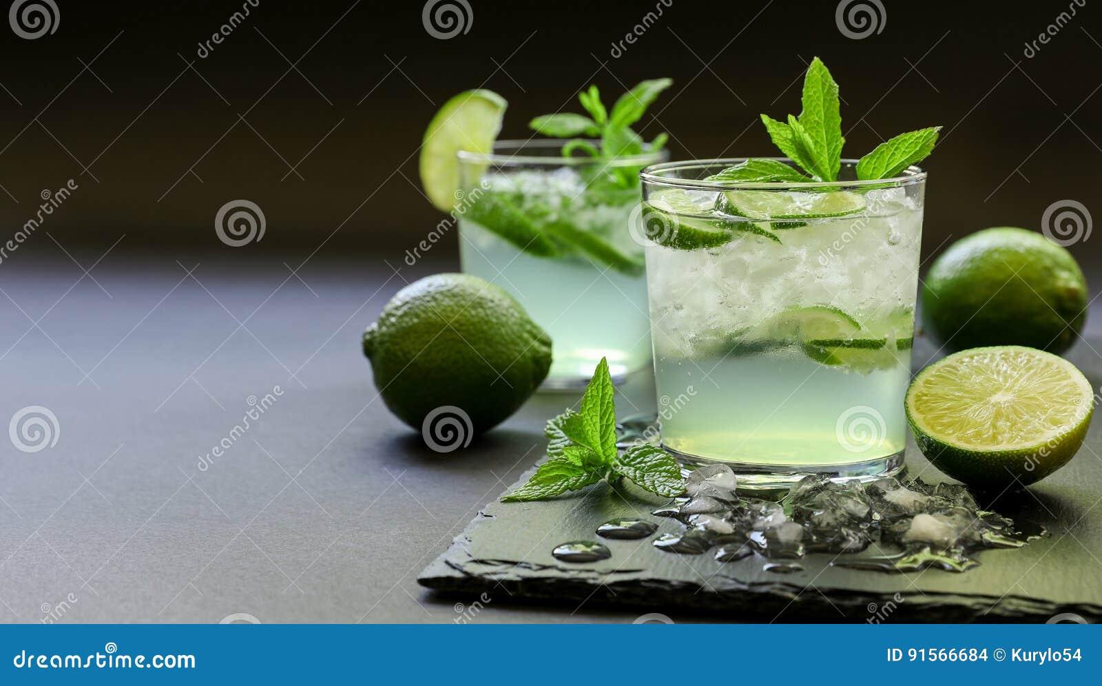 Cóctel frío con el licor del limón, cal, tónico, hielo en fondo oscuro