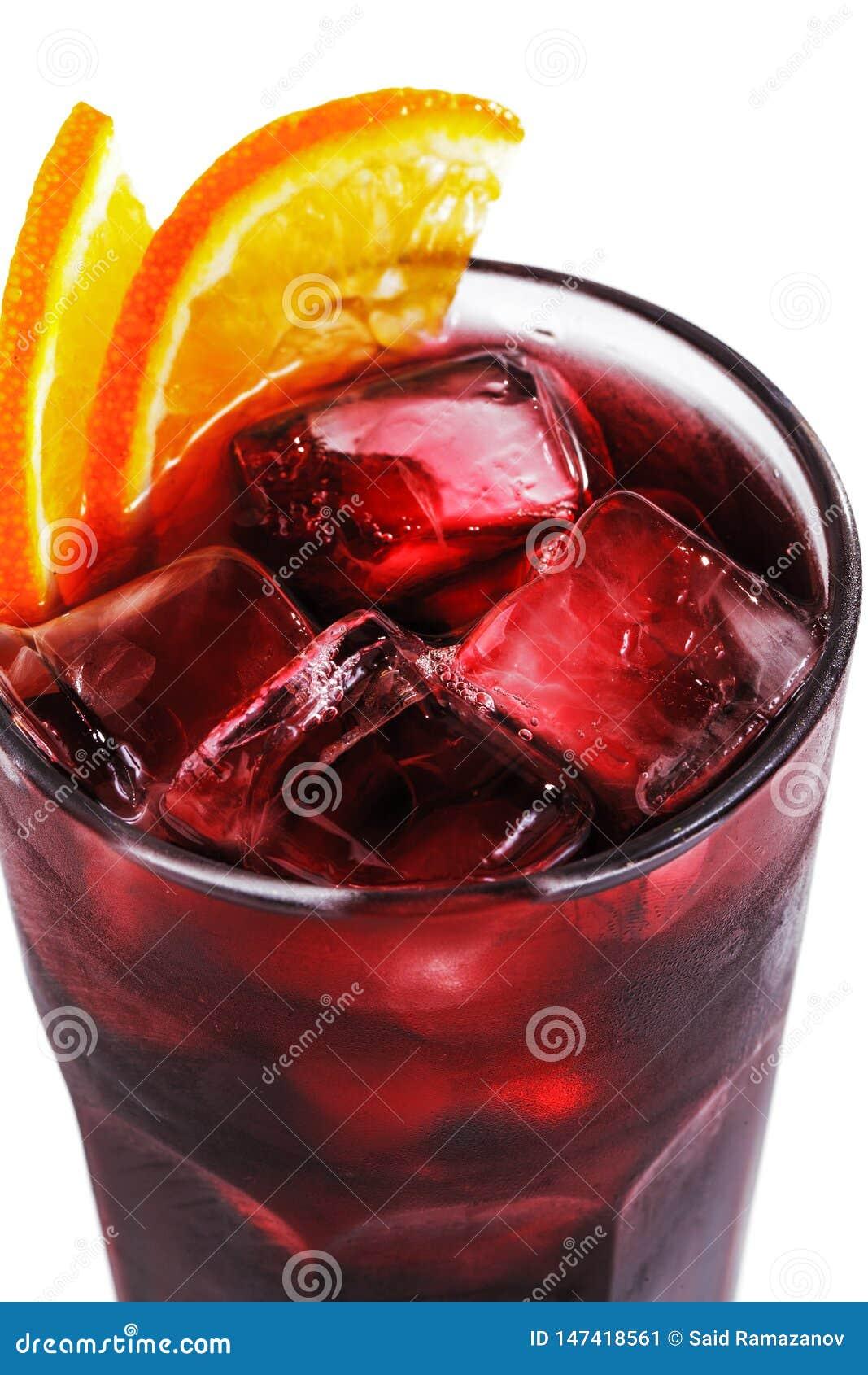 Cóctel rojo con hielo y la naranja en un vidrio en un primer blanco aislado del fondo