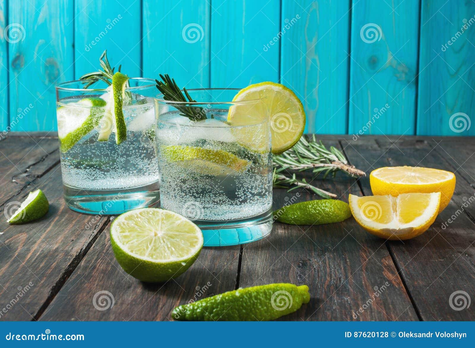 Cóctel tónico de la ginebra de la bebida alcohólica con el limón, el romero y el hielo en la tabla de madera rústica